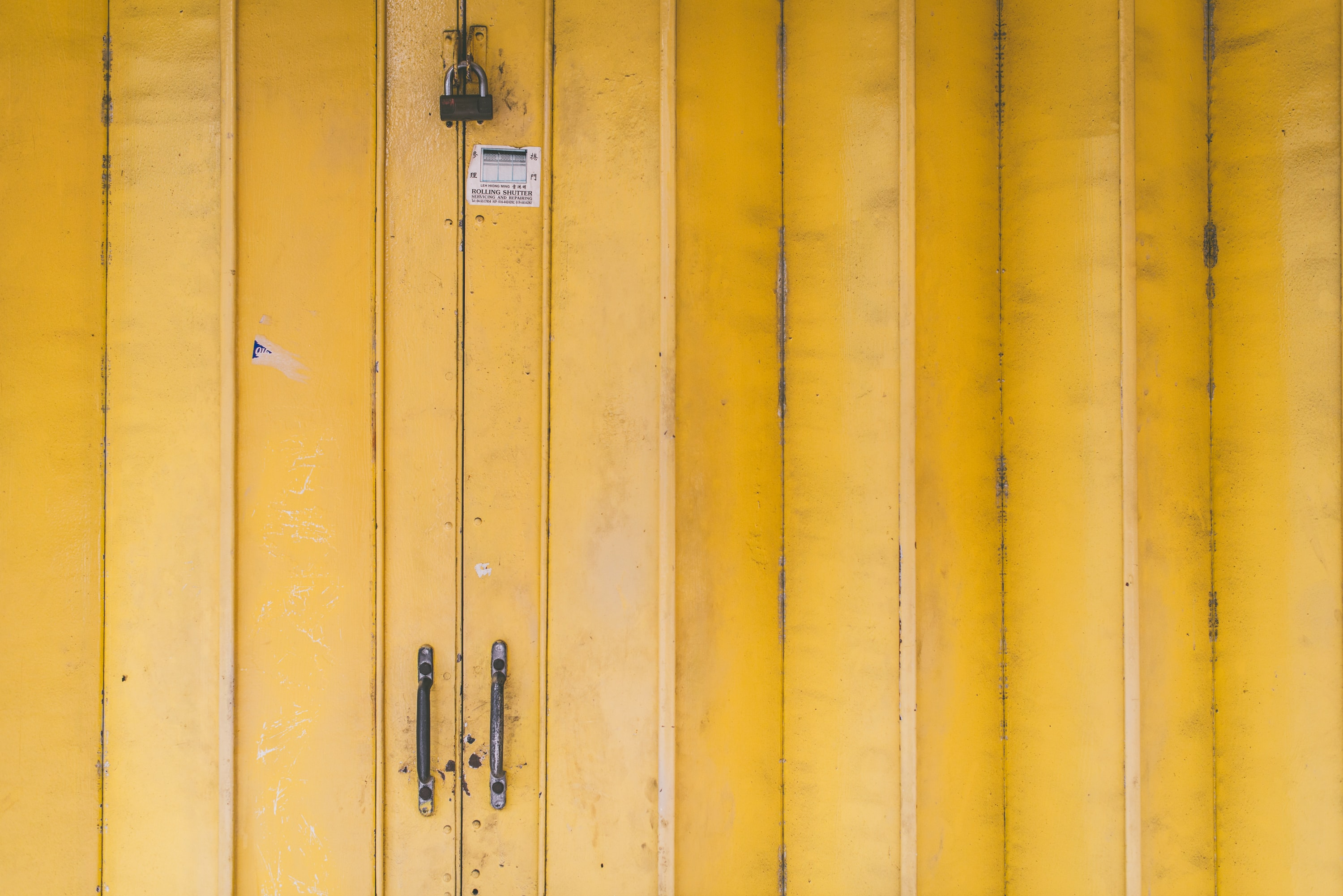 closed yellow wooden door with padlock