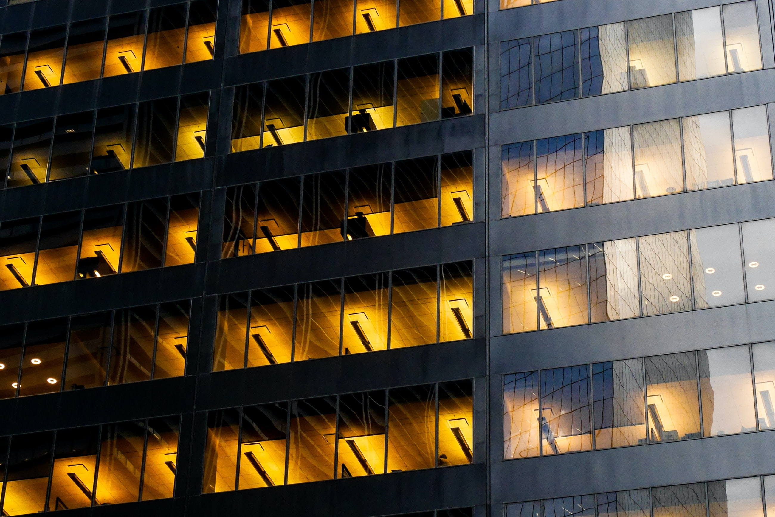 Warm light on several stories of an office building seen from the outside