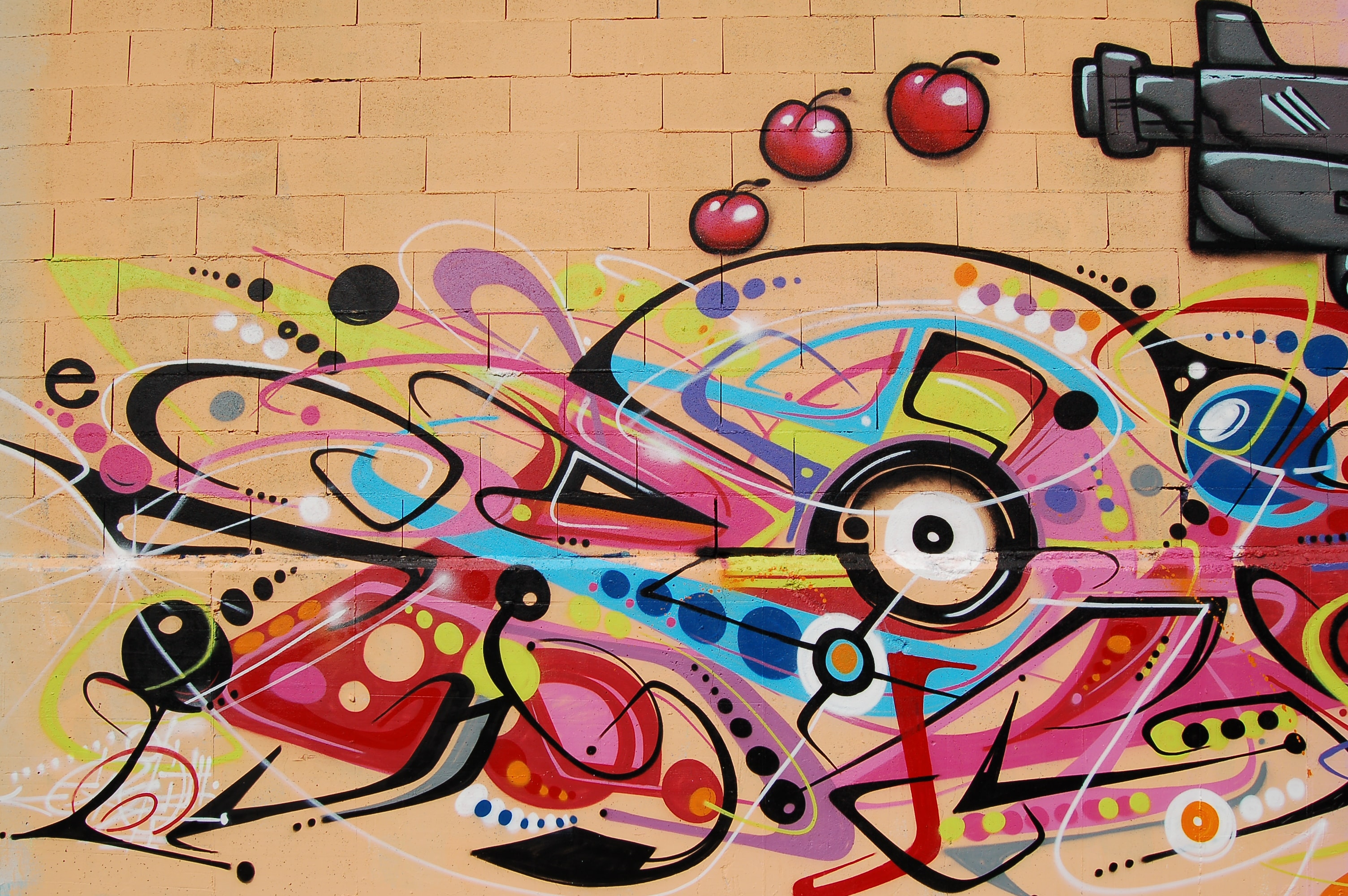 An abstract graffiti wall painting with cherries.