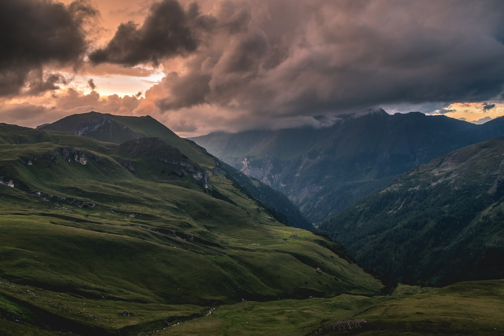 green grass covered mountain under gray clouds