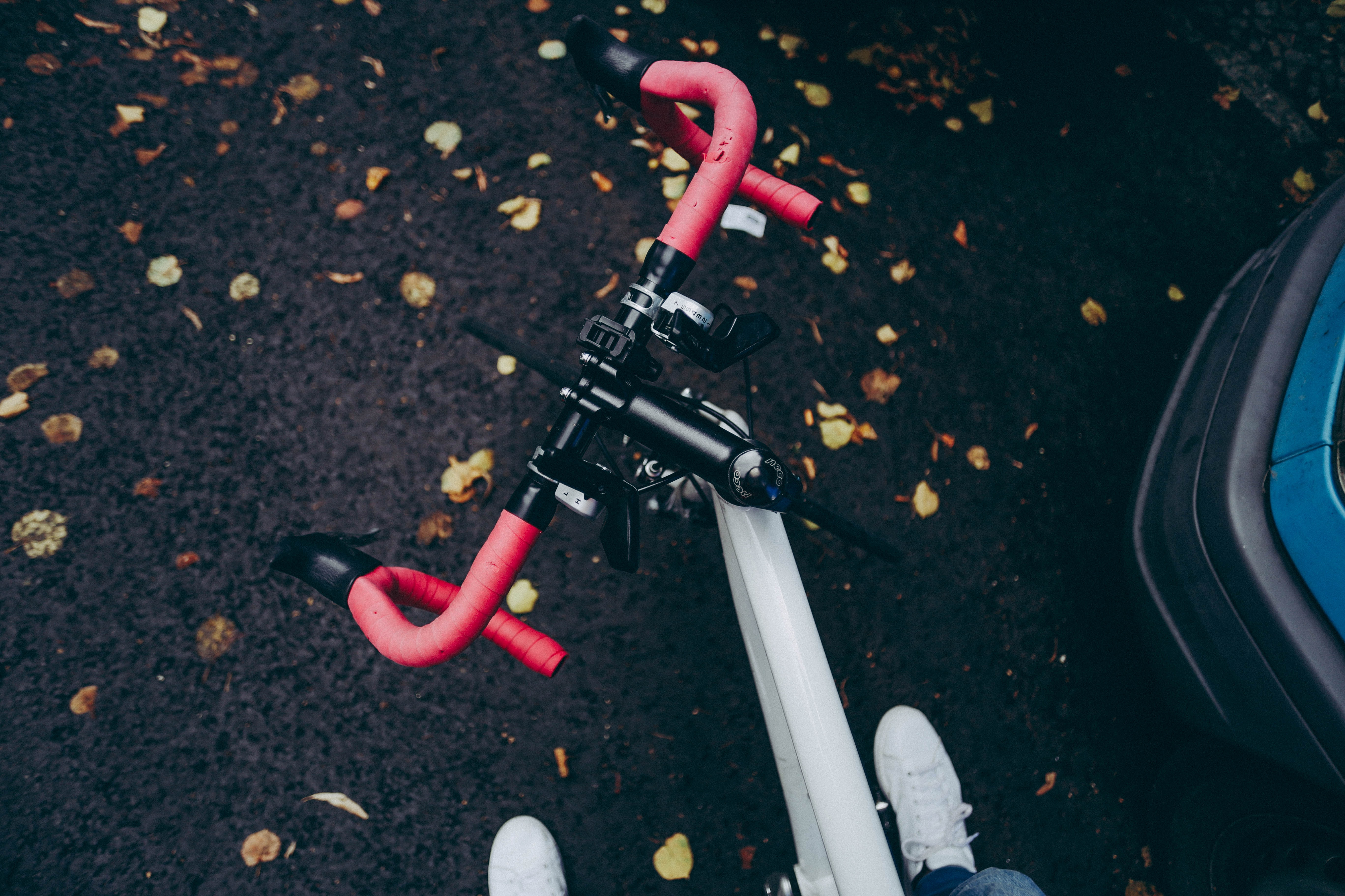 An overhead shot of the handlebars of a racing bike and the shoes of the cyclist.