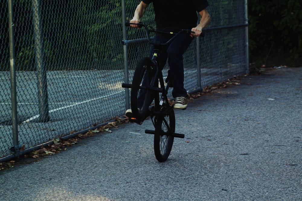 person riding BMX bike near chain link fence