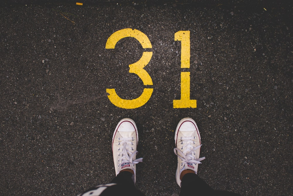 person standing beside 31 painted gray concrete road at daytime