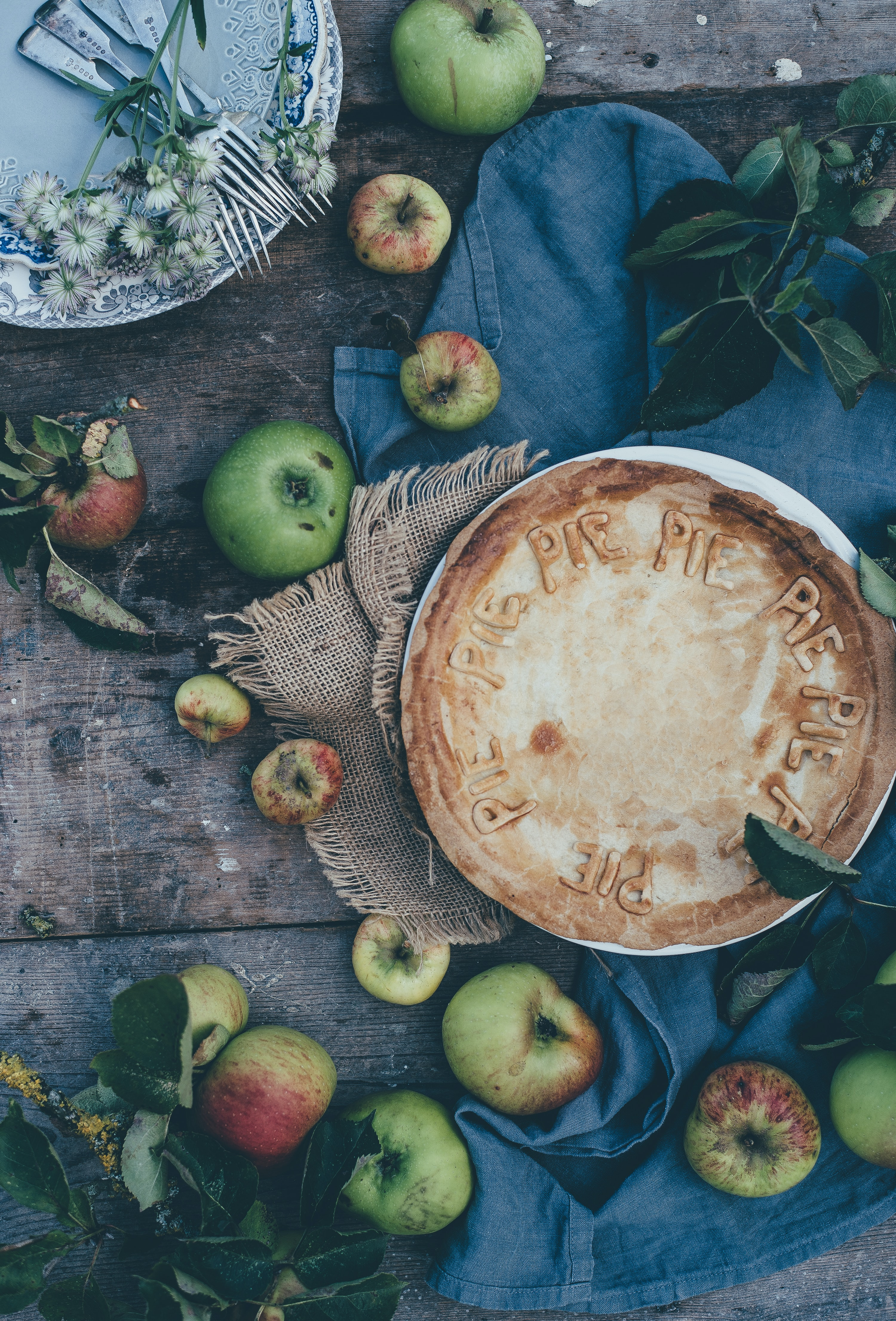 Top view of a perfectly baked apple pie dessert with green and red apples surrounding it on a wooden table.