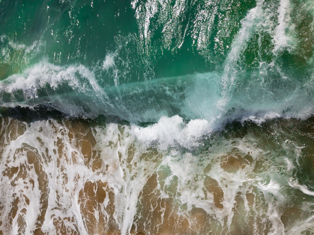 aerial photography of sea waves on seashore during daytime