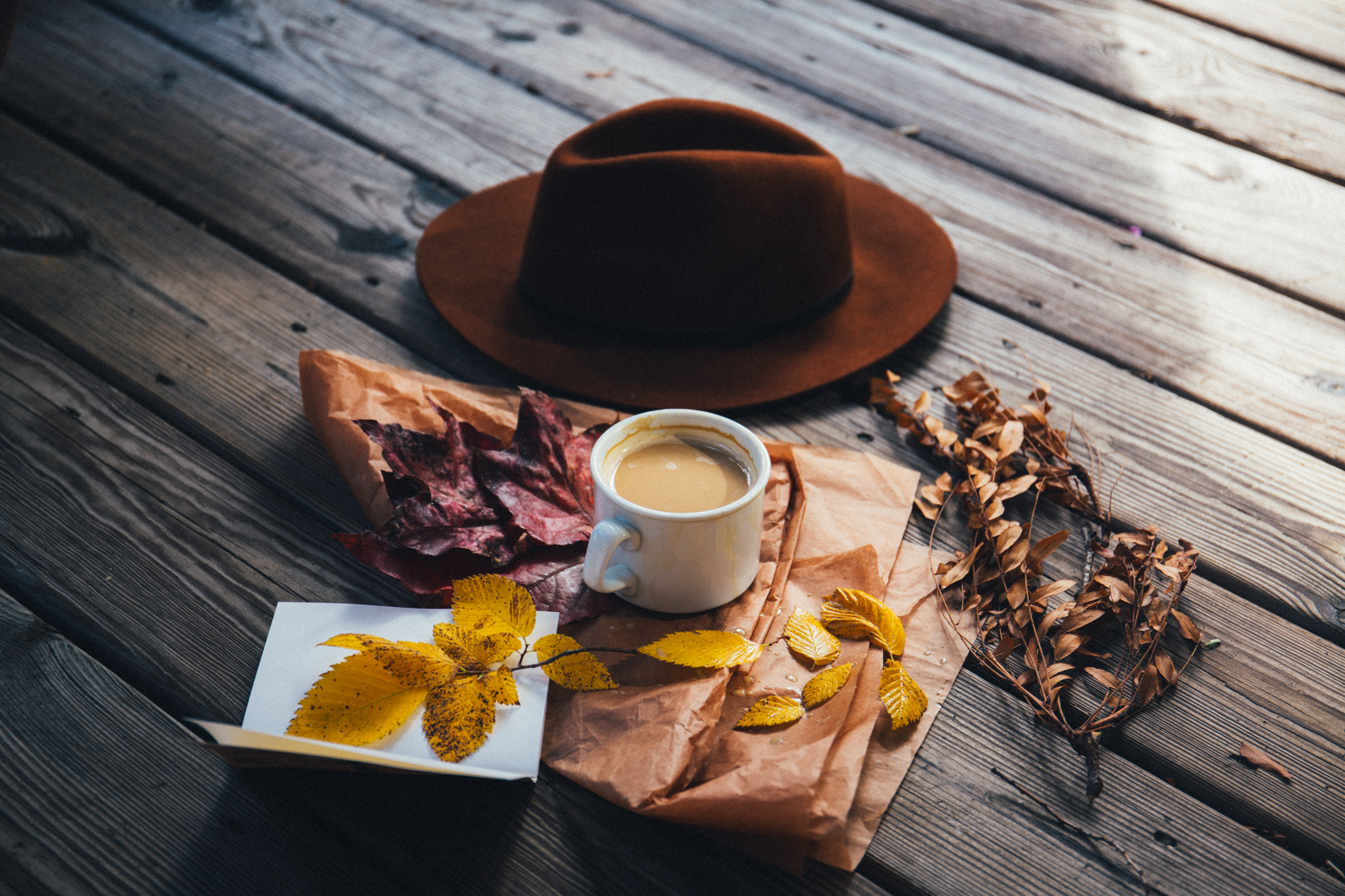 A brown cowboy hat, a cup of coffee and autumn leaves laid out on a wooden surface