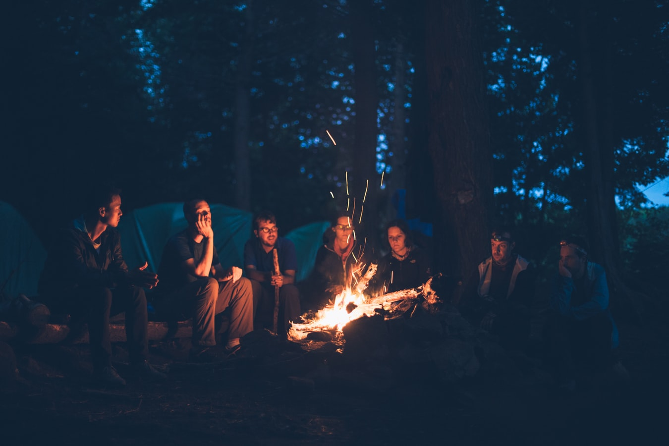 people sitting around a bonfire