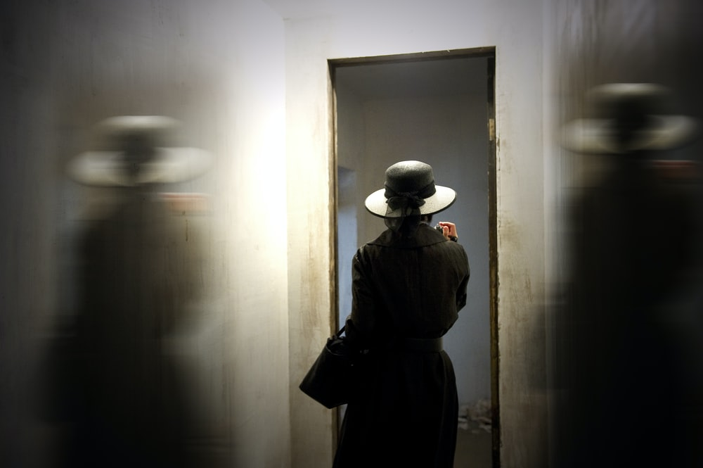 person wearing hat carrying bag while standing in front of door