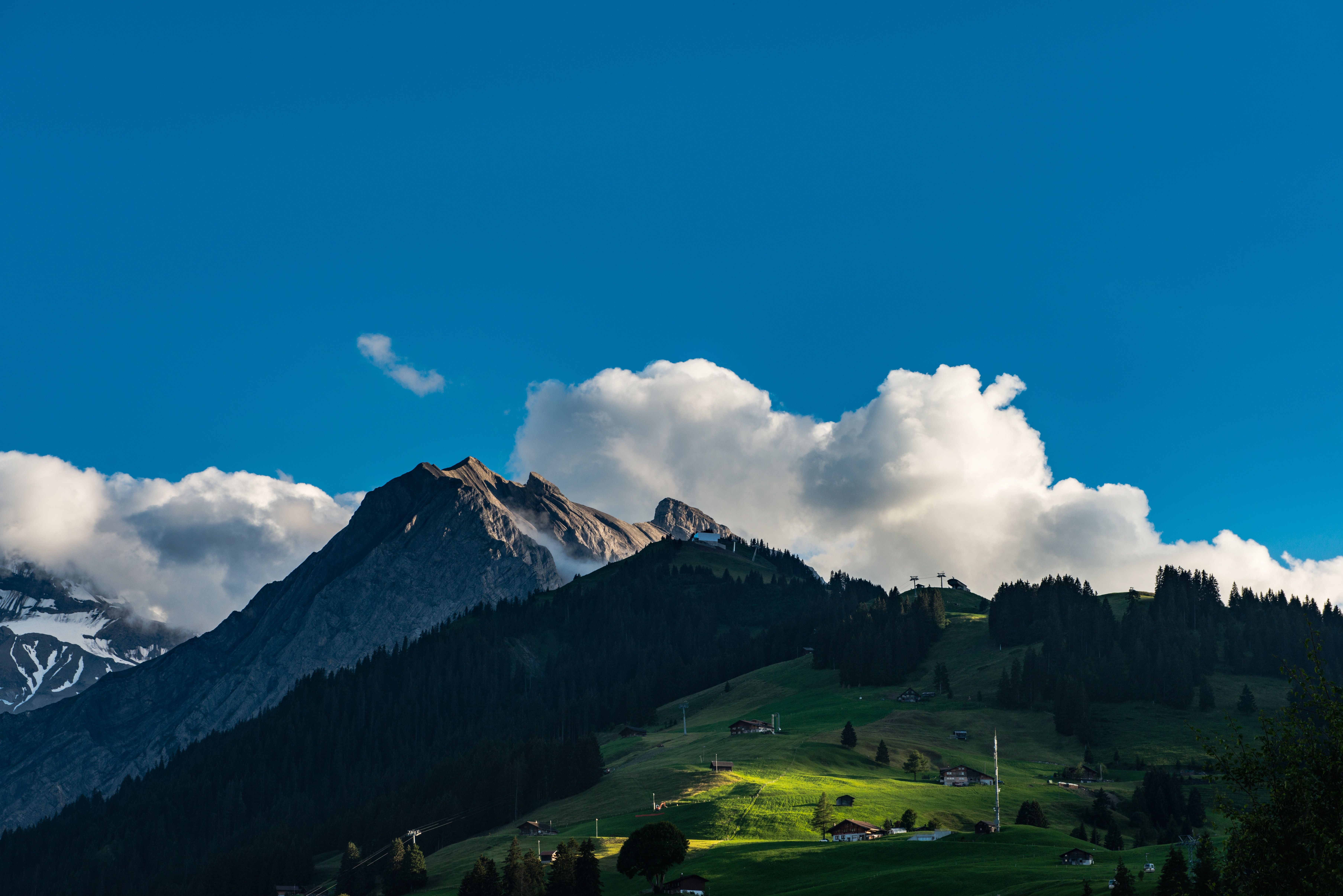 A grassy mountain shot with the clouds beyond the peak in Adelboden village