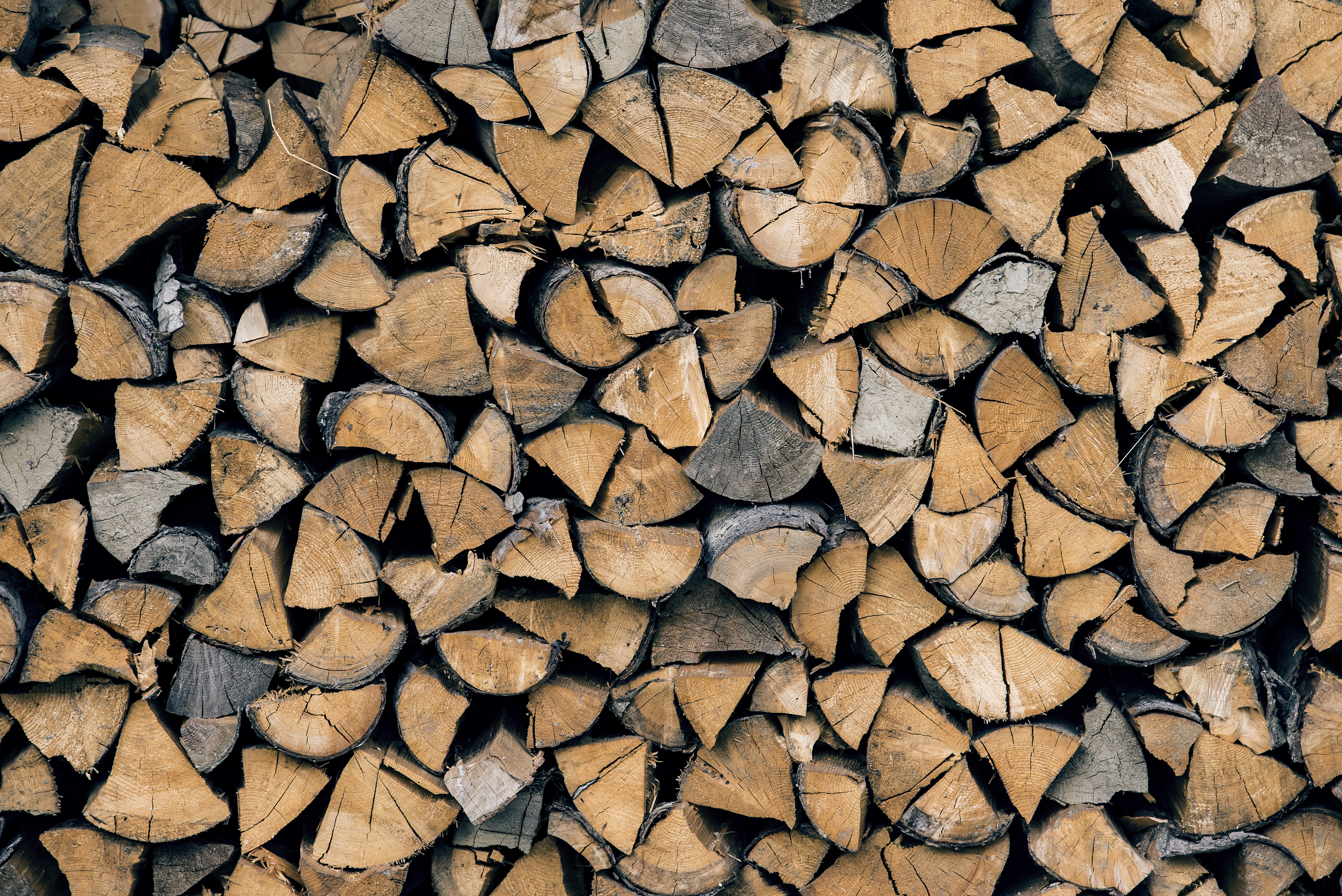 A stack of wedge-shaped firewood pieces