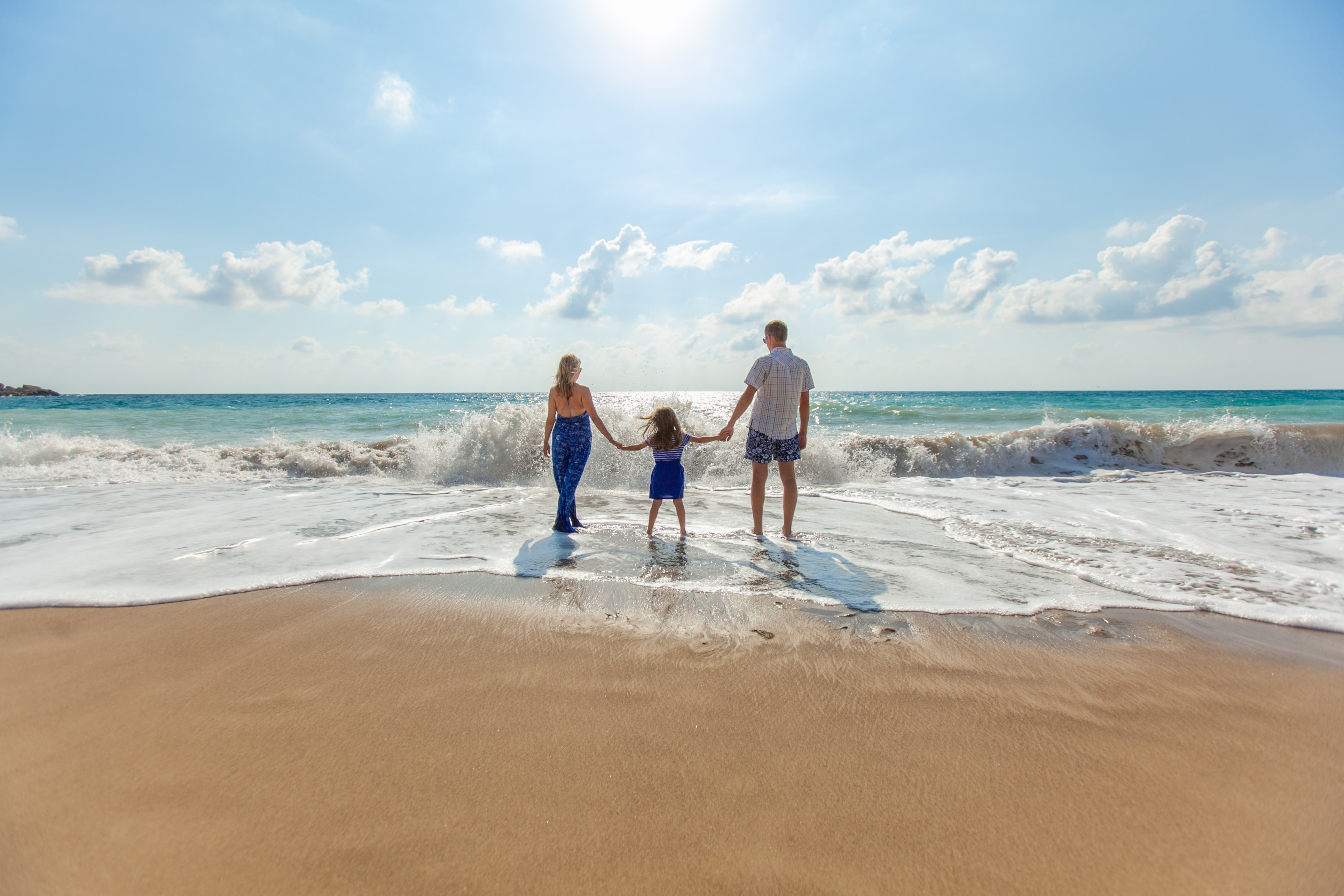 Mother, daughter and father holding hands in a line on a beach during the daytime.