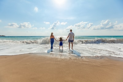 man, woman and child holding hands on seashore holiday teams background
