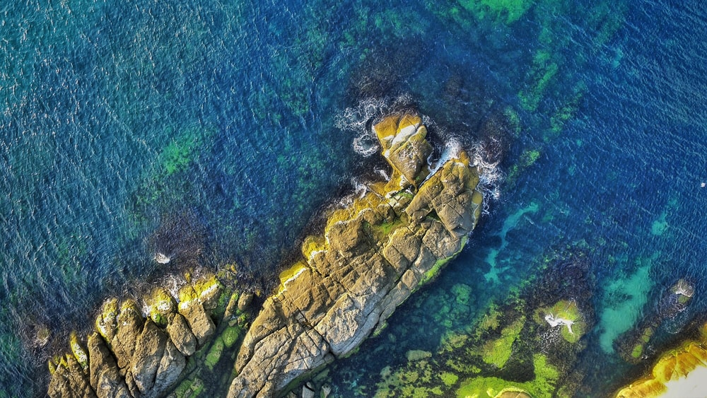 aerial view photography of rock formations surrounded by ocean during daytime