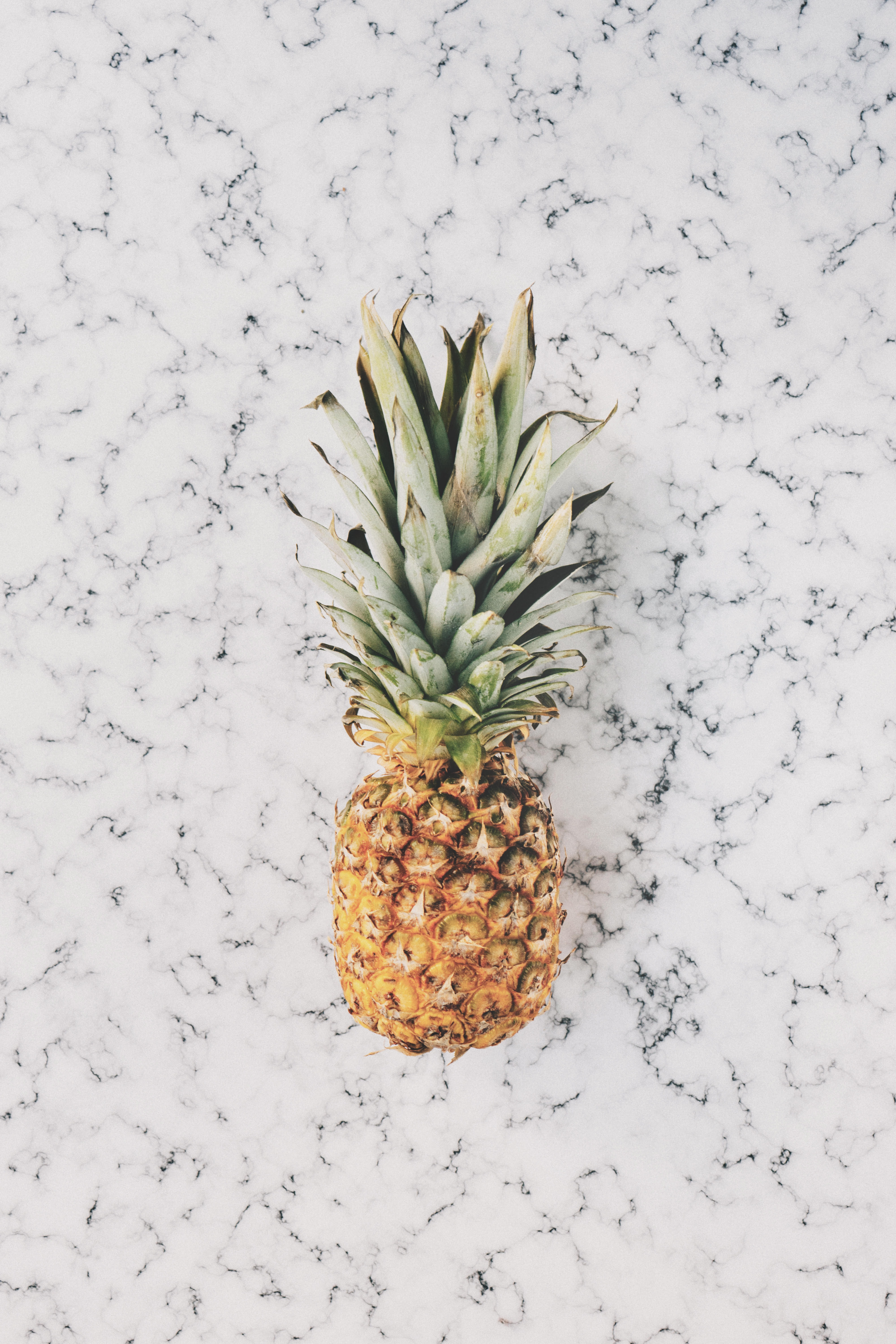 A pineapple sitting on a white countertop.