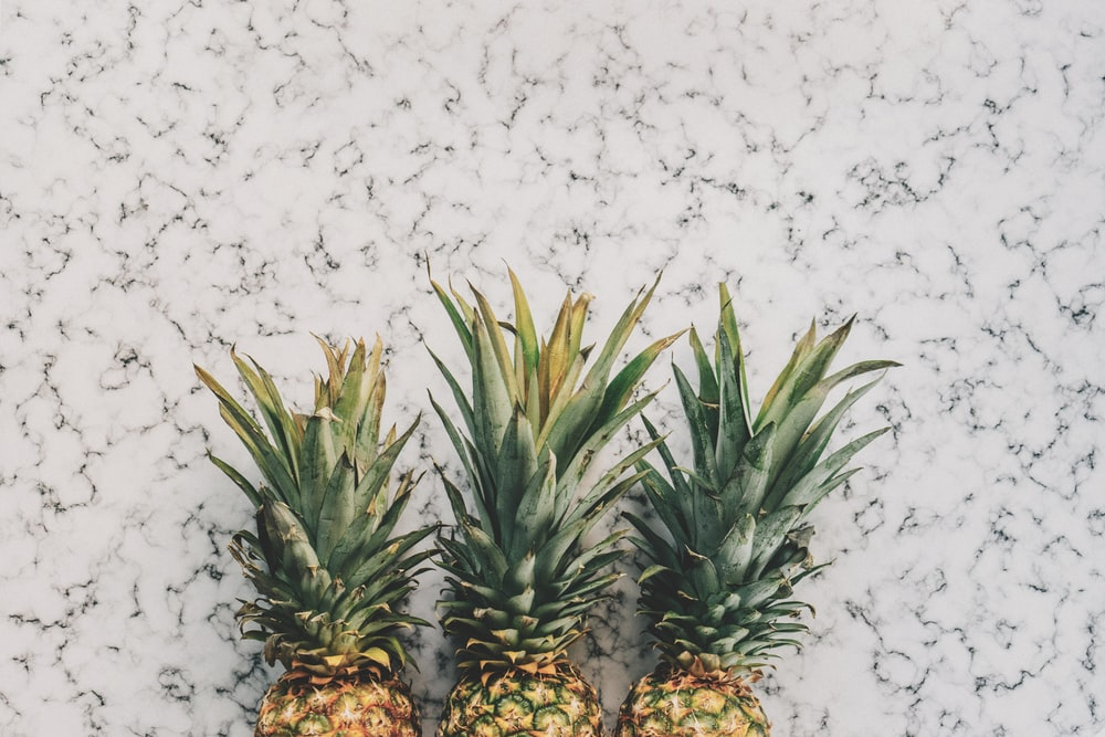 three yellow pineapple fruits on white surface