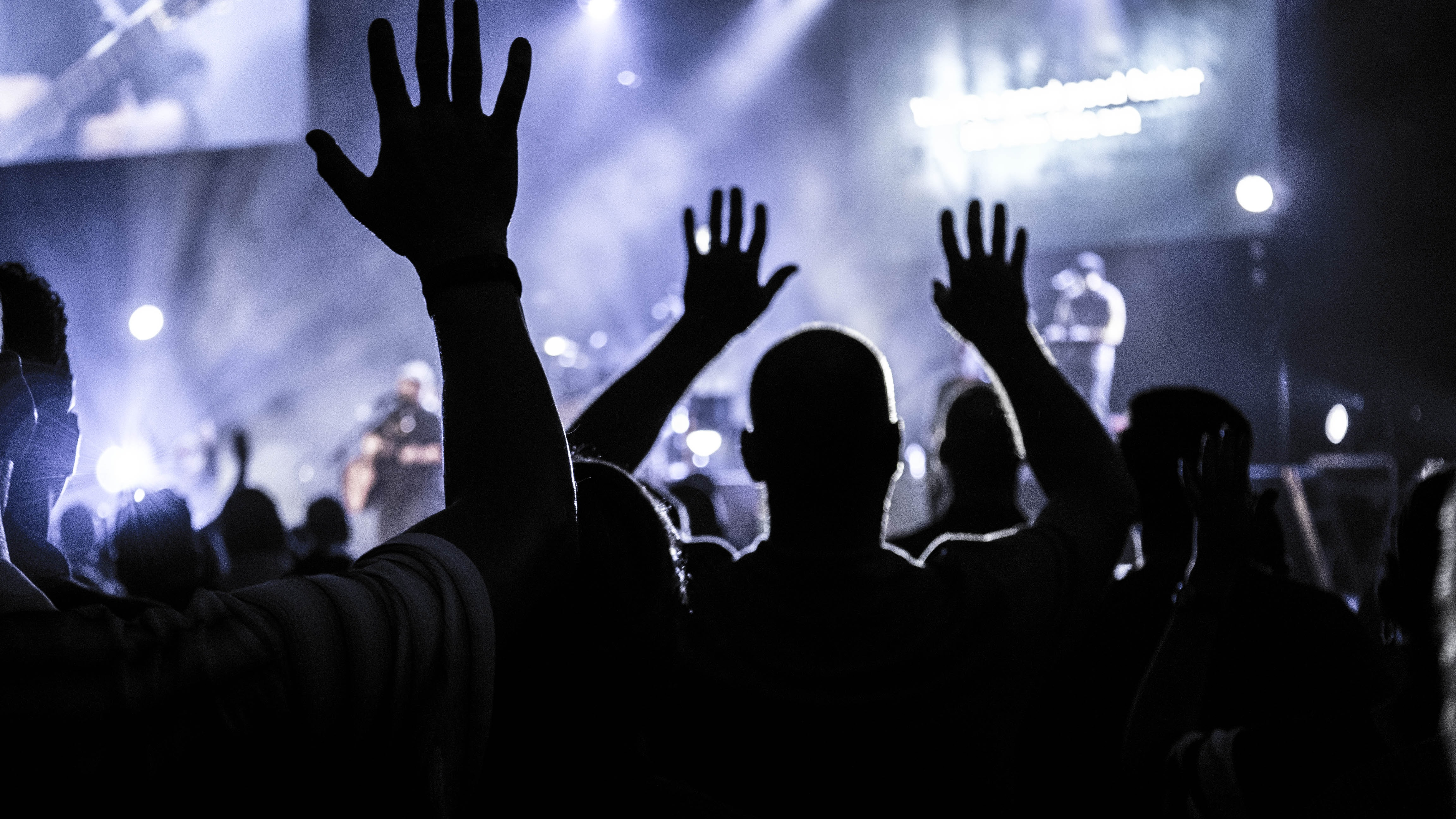 Concertgoers raising their open hands in the air silhouetted against the illuminated stage in Houston