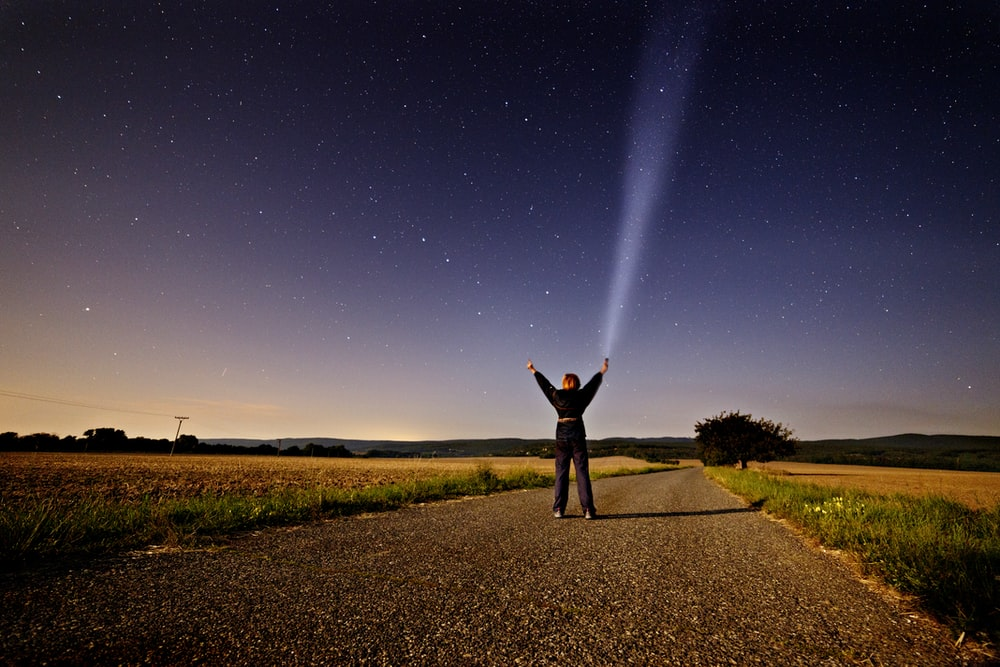 person raising his two hands while holding flashlight standing on road between grass during sunset