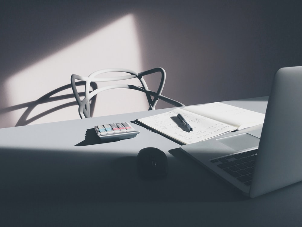 A modern white chair at a table with a laptop, a notebook and a calculator