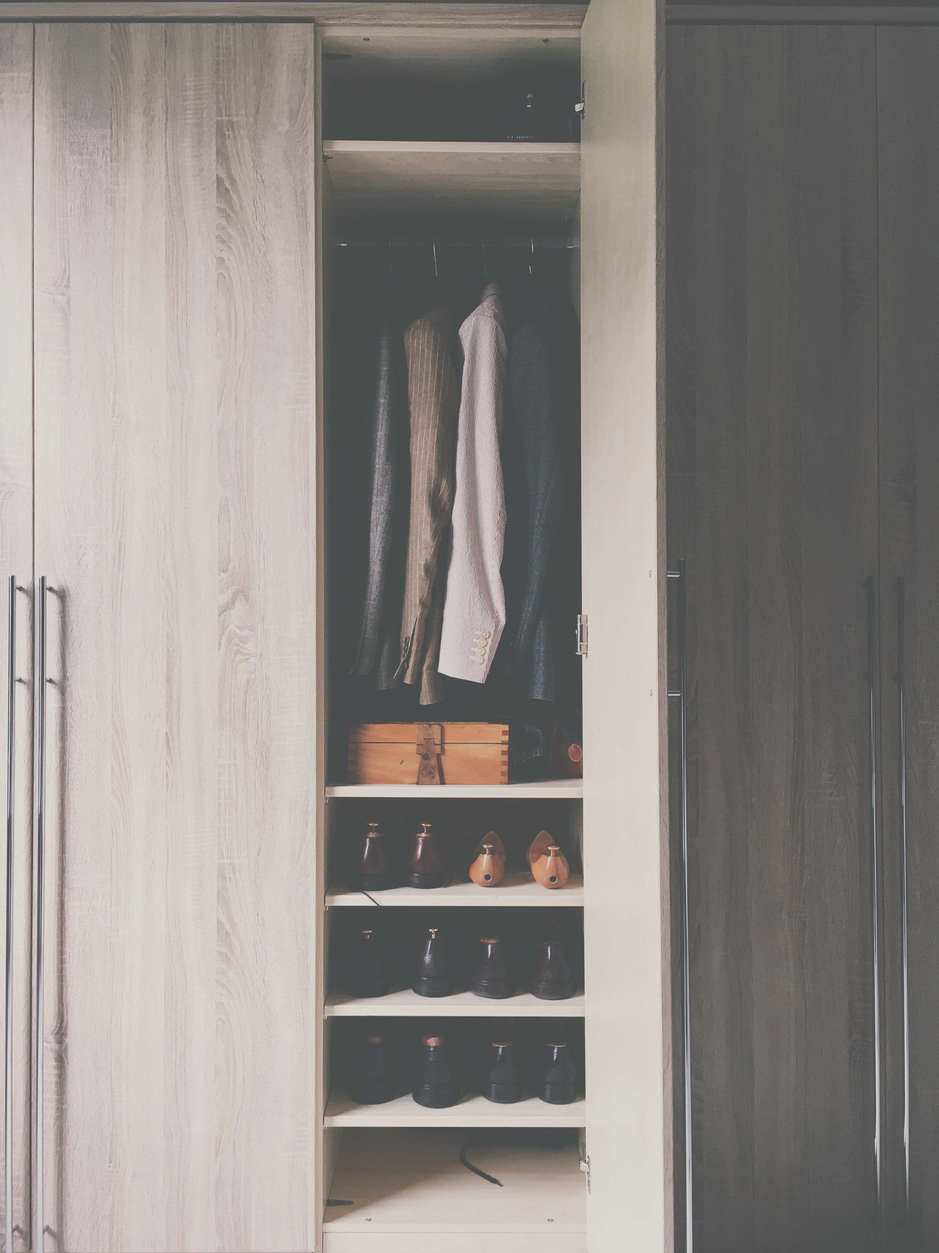 A monochromatic wooden closet with silver handles filled with shoes, a wooden box, and suit jackets in Wilmslow, England, United Kingdom