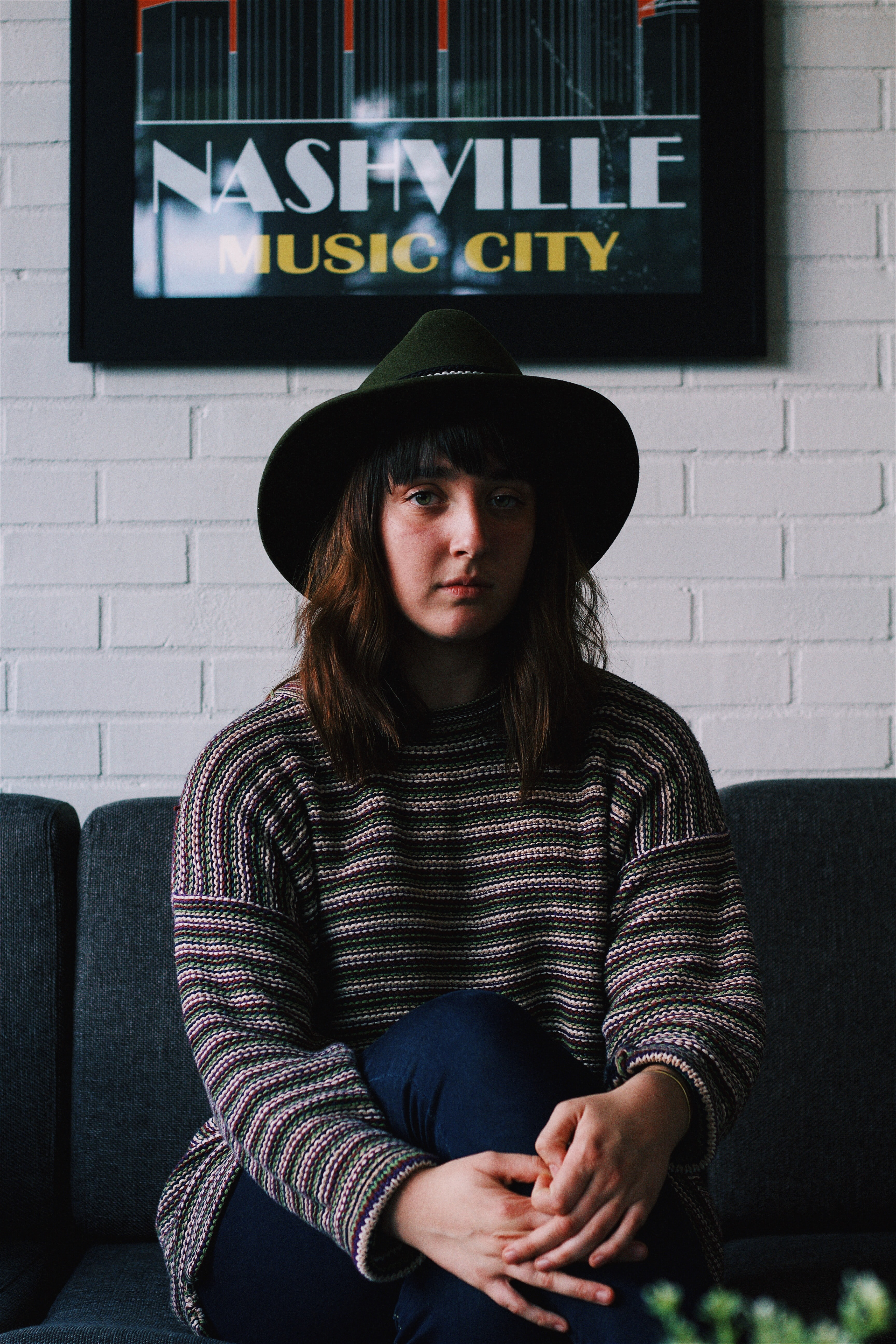 """A young woman in a hat sitting on a sofa under a white wall with a """"Nashville Music City"""" poster"""