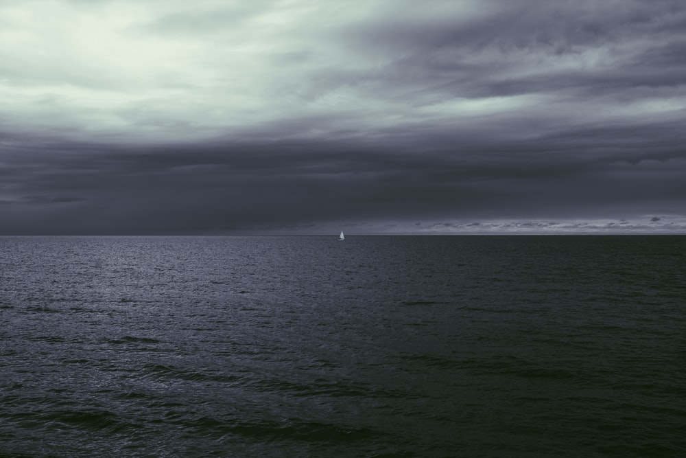 white boat on sea under gray clouds