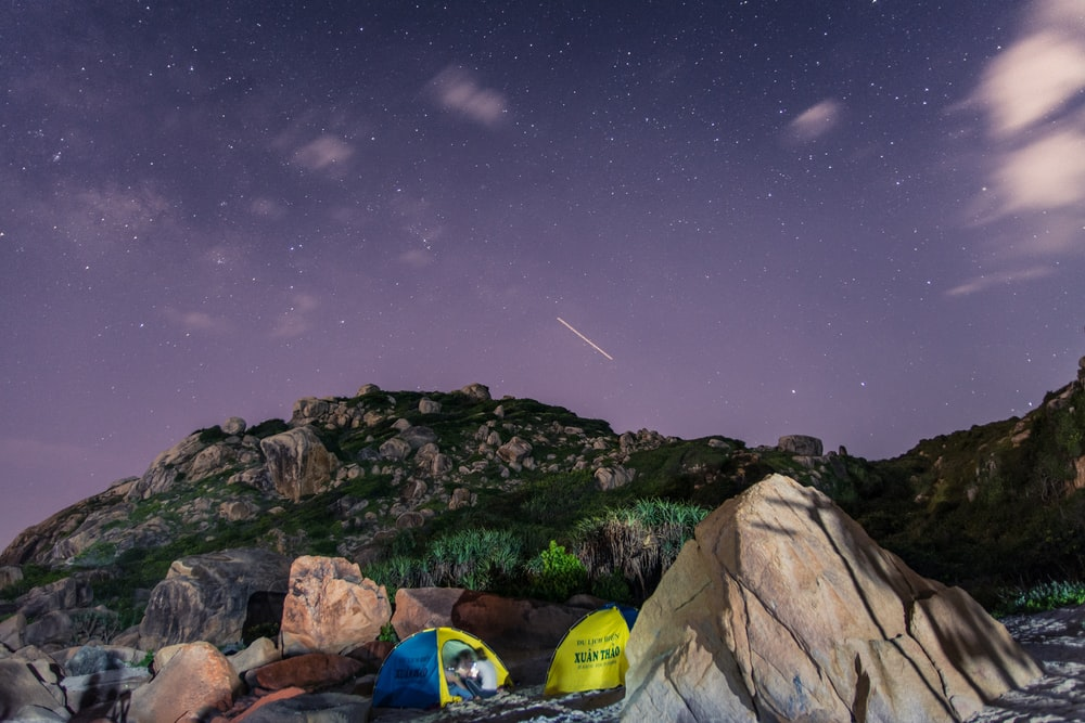 tents surrounded with green rocks under purple sky at night