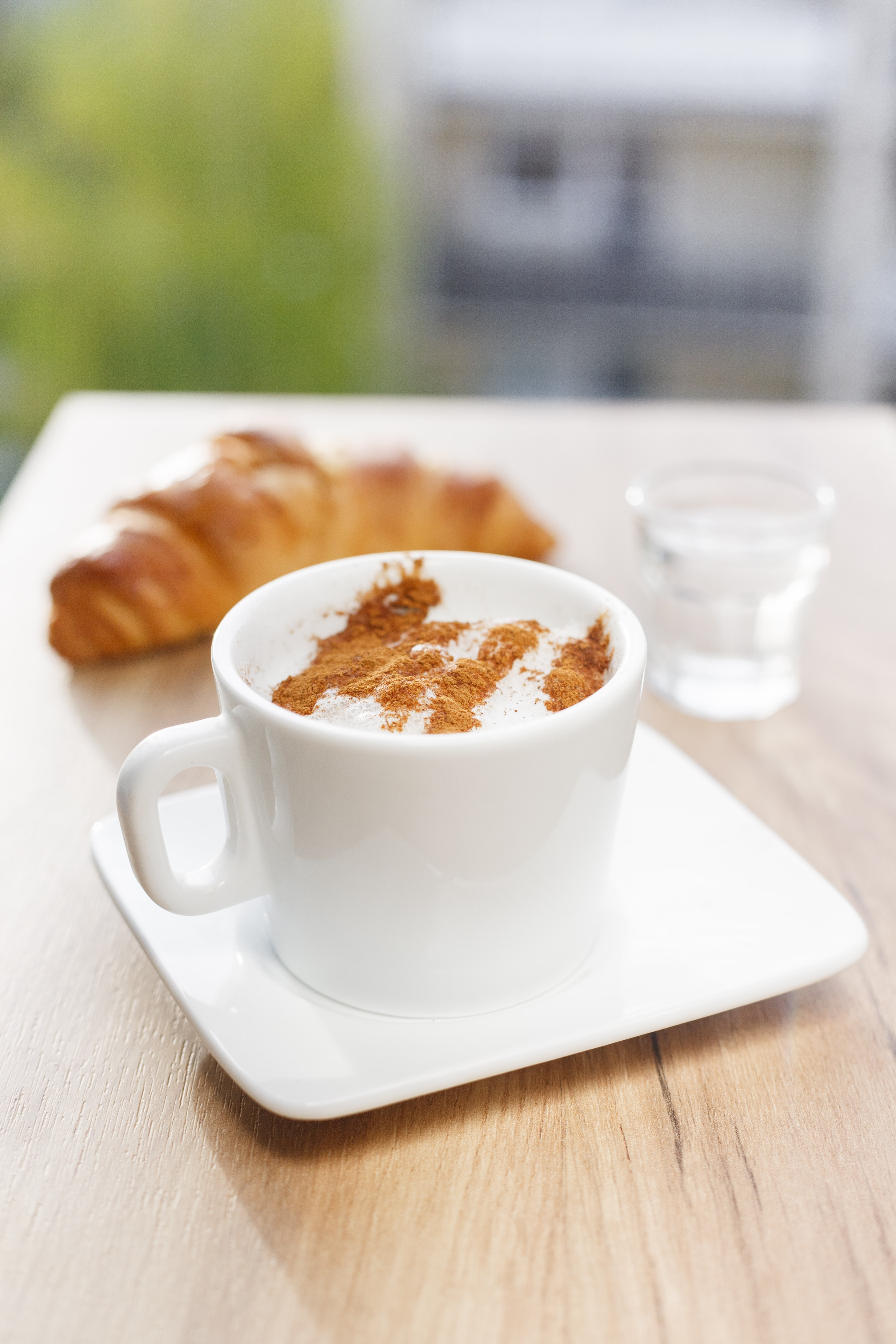 Cappuccino in a white mug and saucer with cinnamon on top and a croissant in the background
