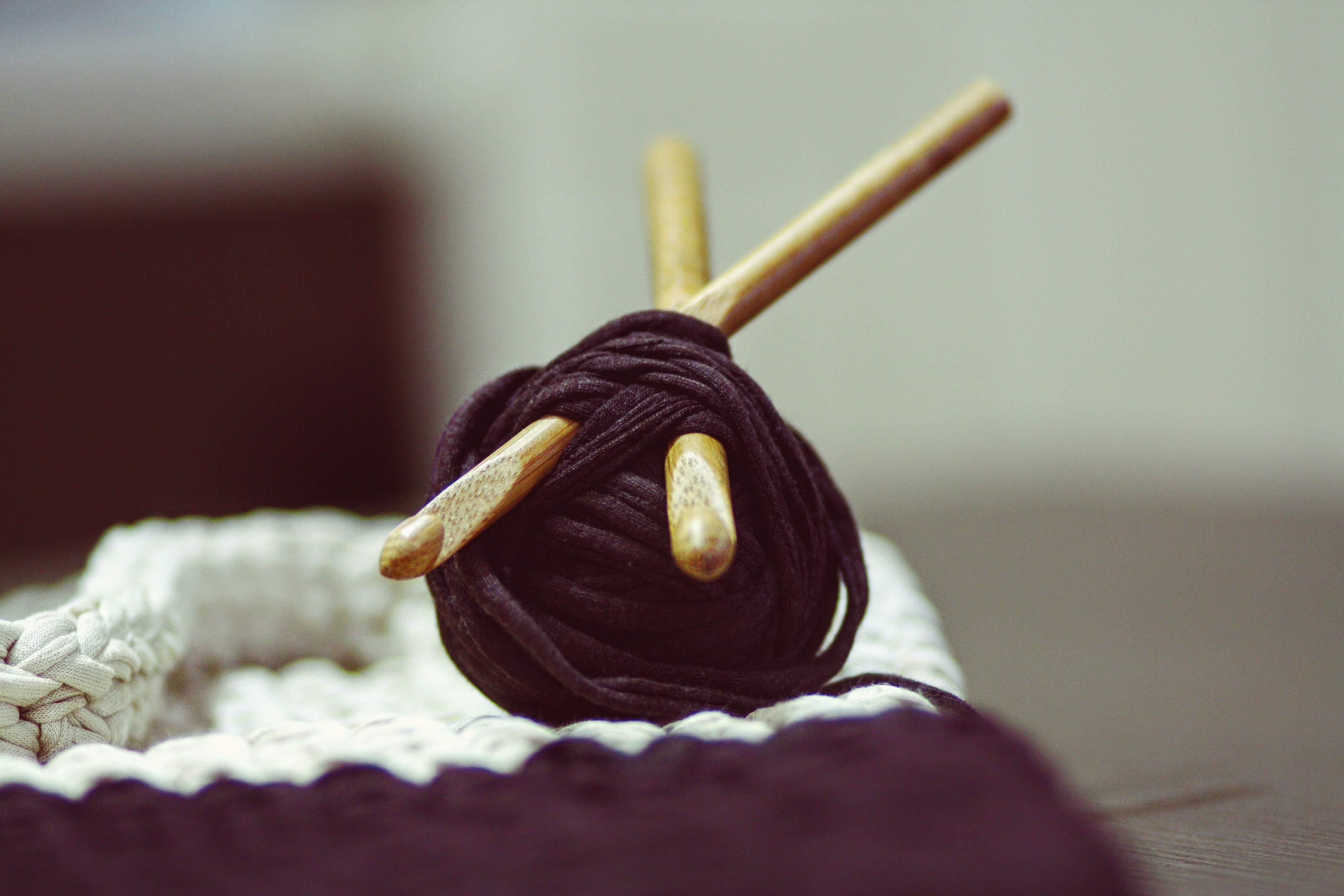 A roll of yarn with wooden knitting needles pierced through next to a weaved fabric