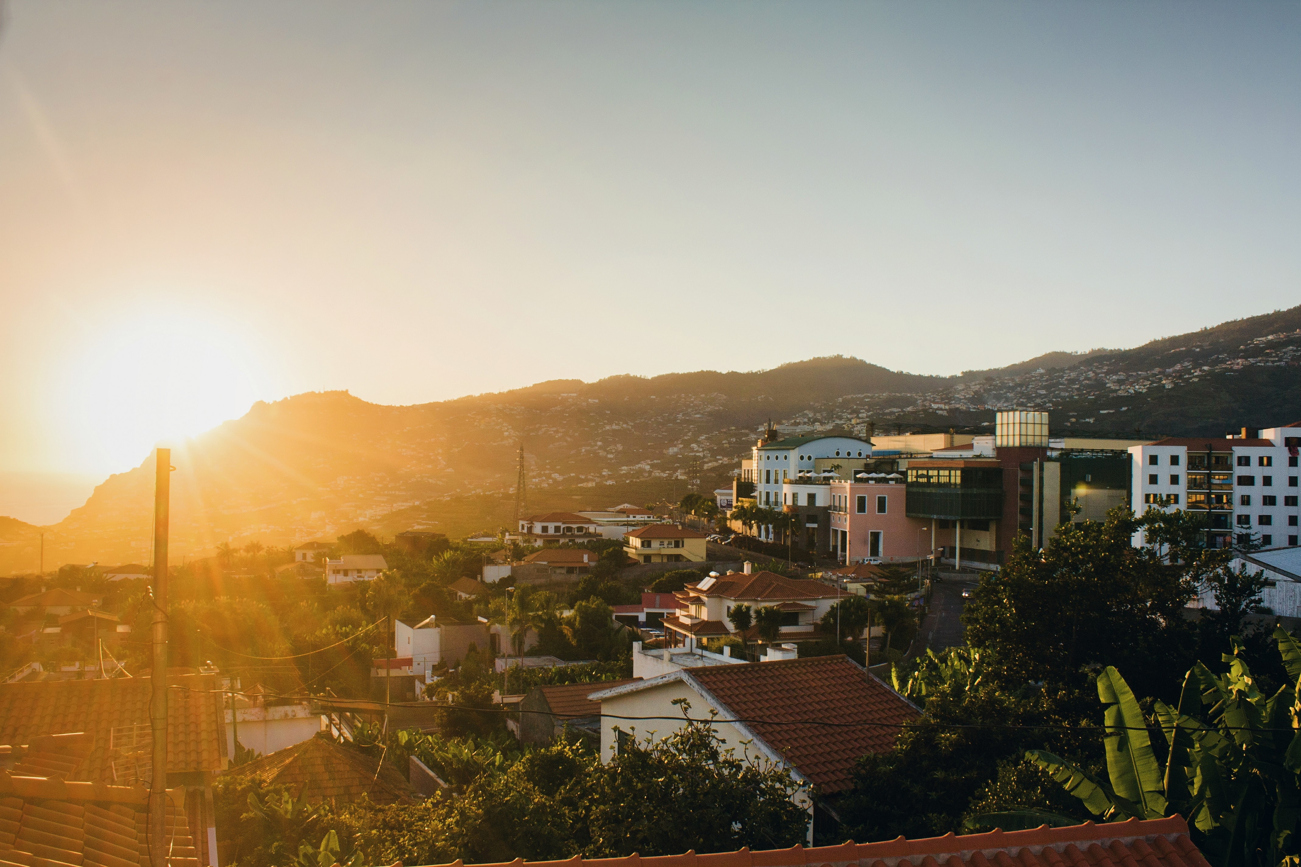 The sunrise-or-sunset over city rooftop, building tree and hillside on Madeira Island