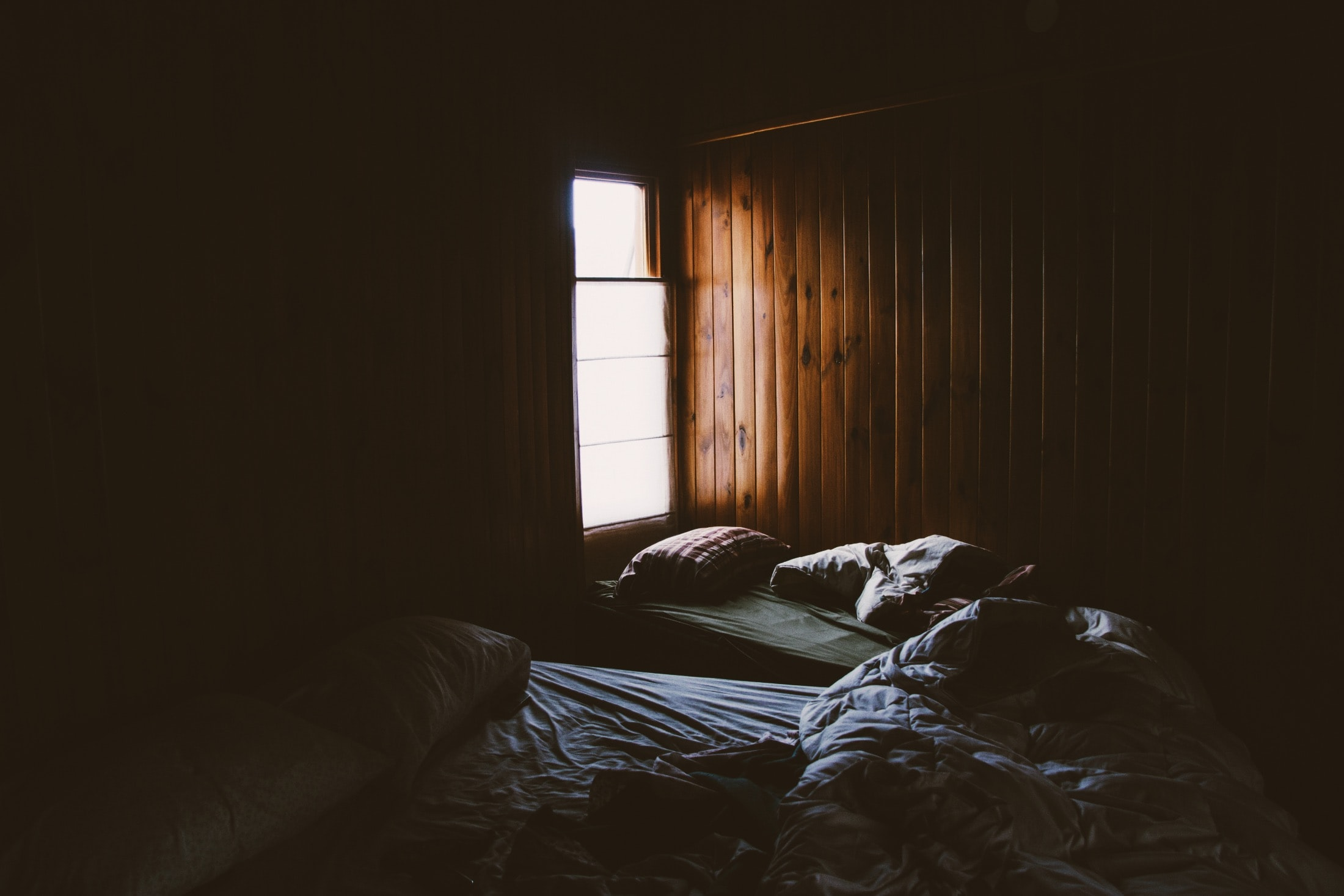 Pale light pouring into a cabin through a small window illuminates two unmade beds