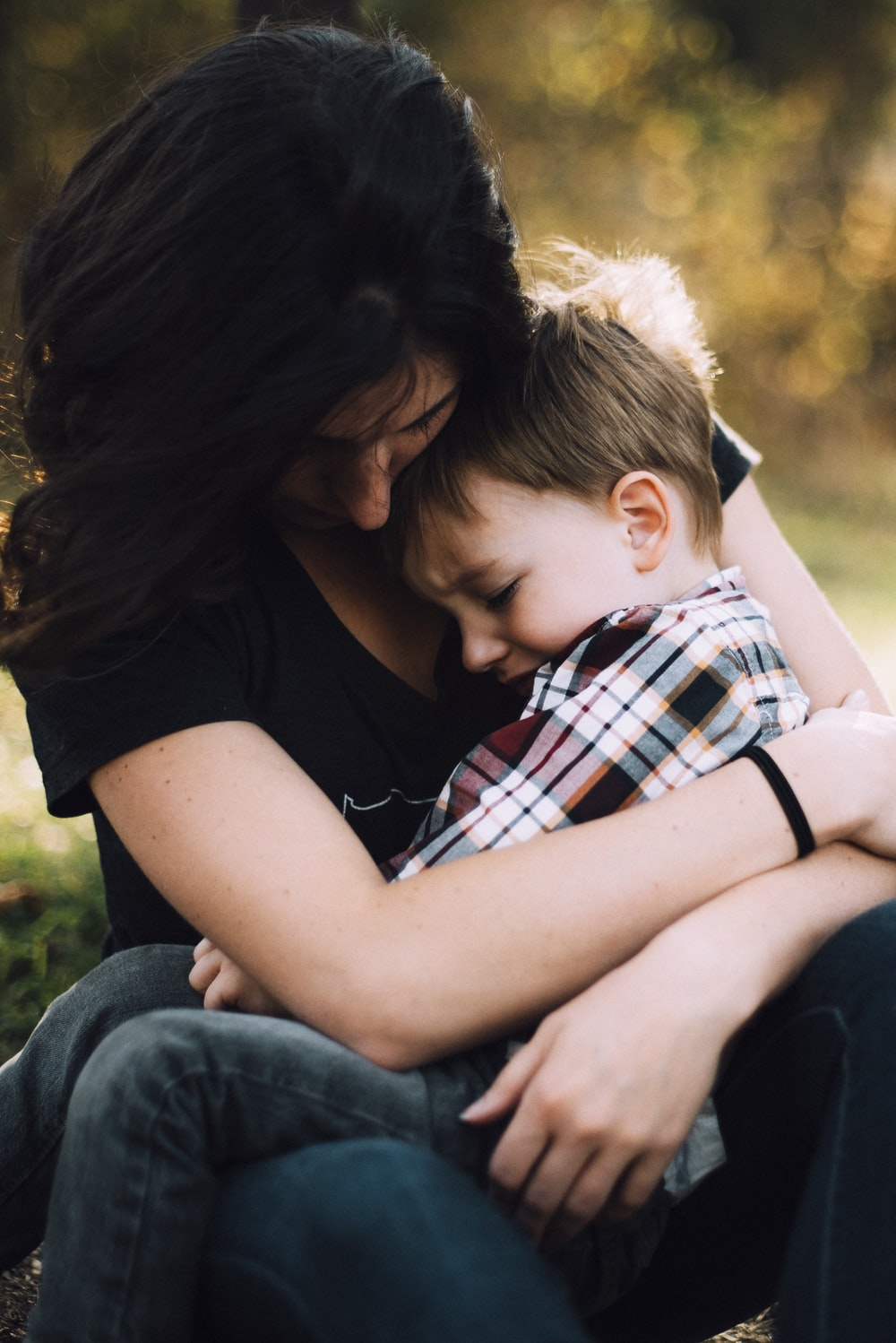 woman hugging boy on her lap