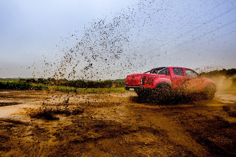 red 4-door truck on mud near trees under cloudy sky