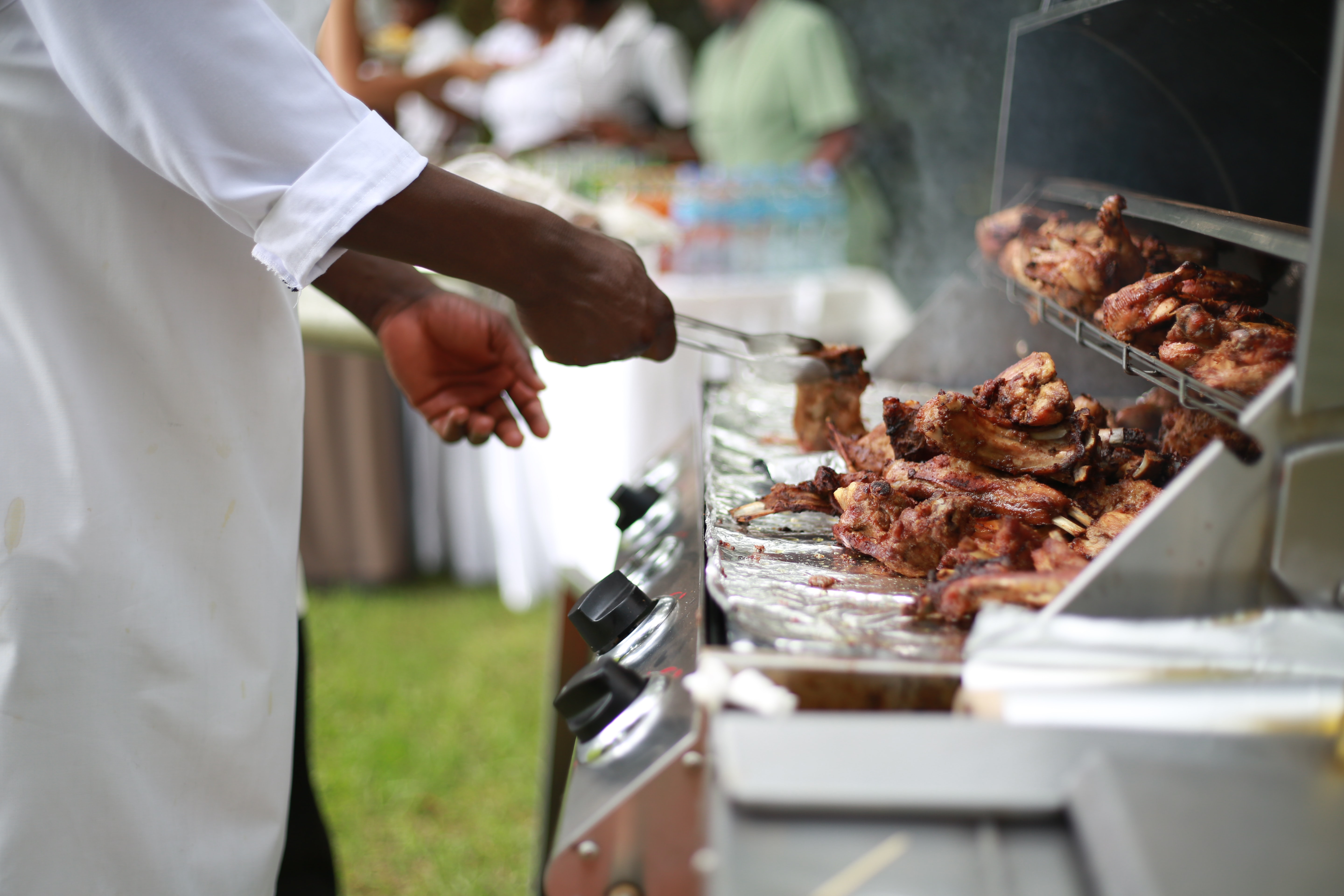 person in white shirt grilling meat
