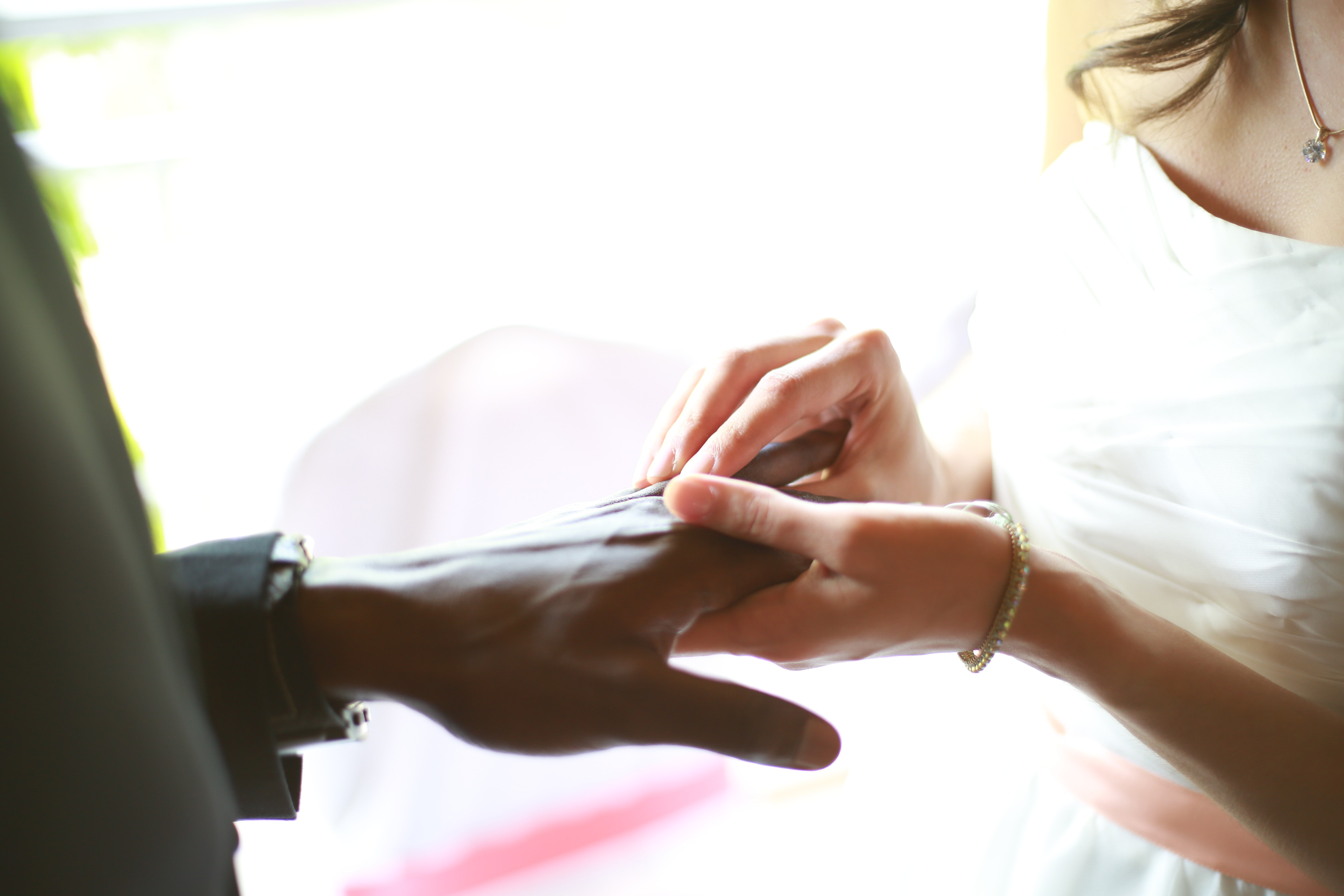 Bride slides the ring onto the hand of her groom on a sunlit morning