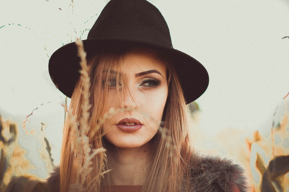 woman wearing black hat standing beside beige grass