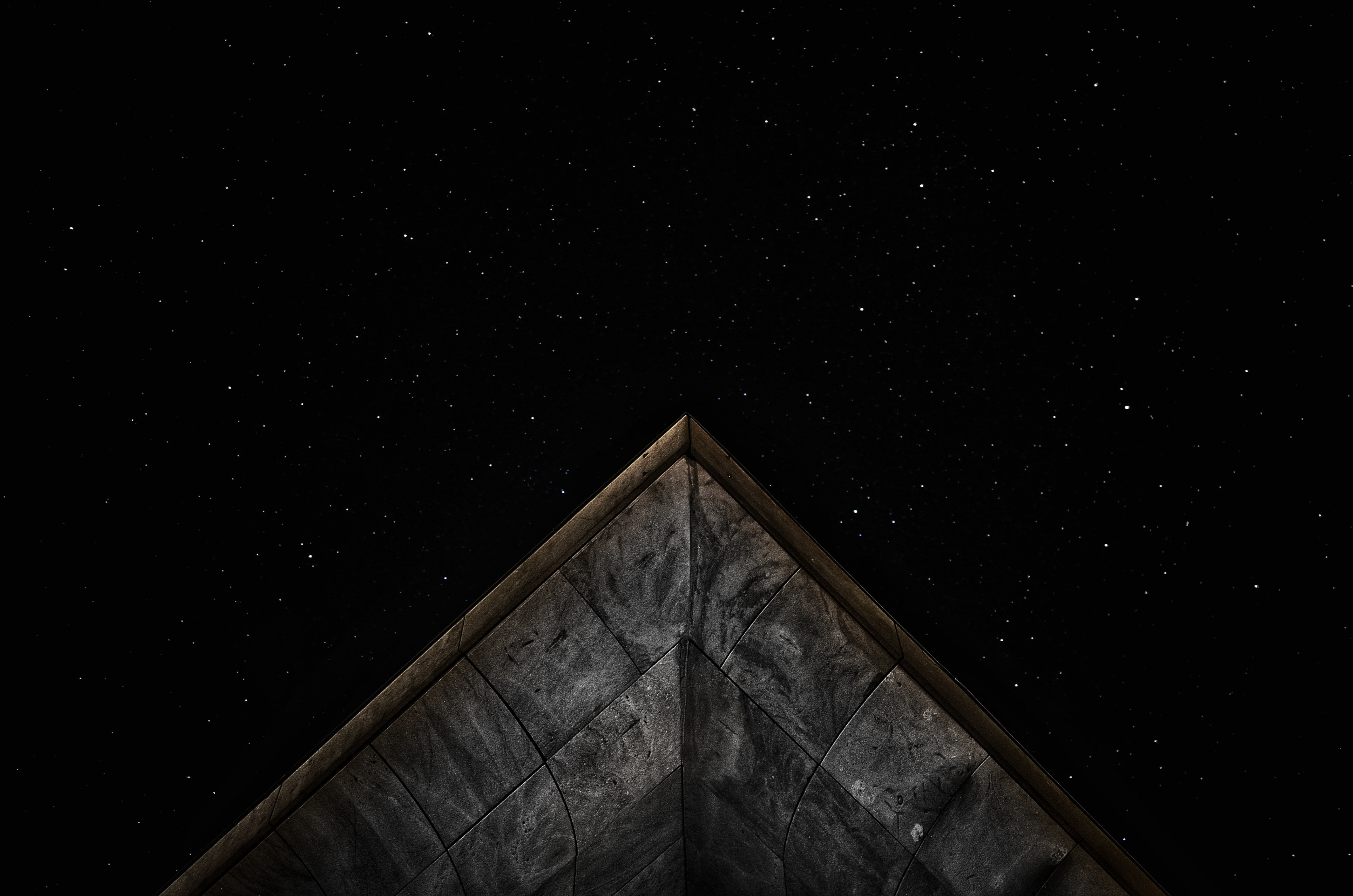 The peak of the roof of a stone building against the starry night in Sardegna.