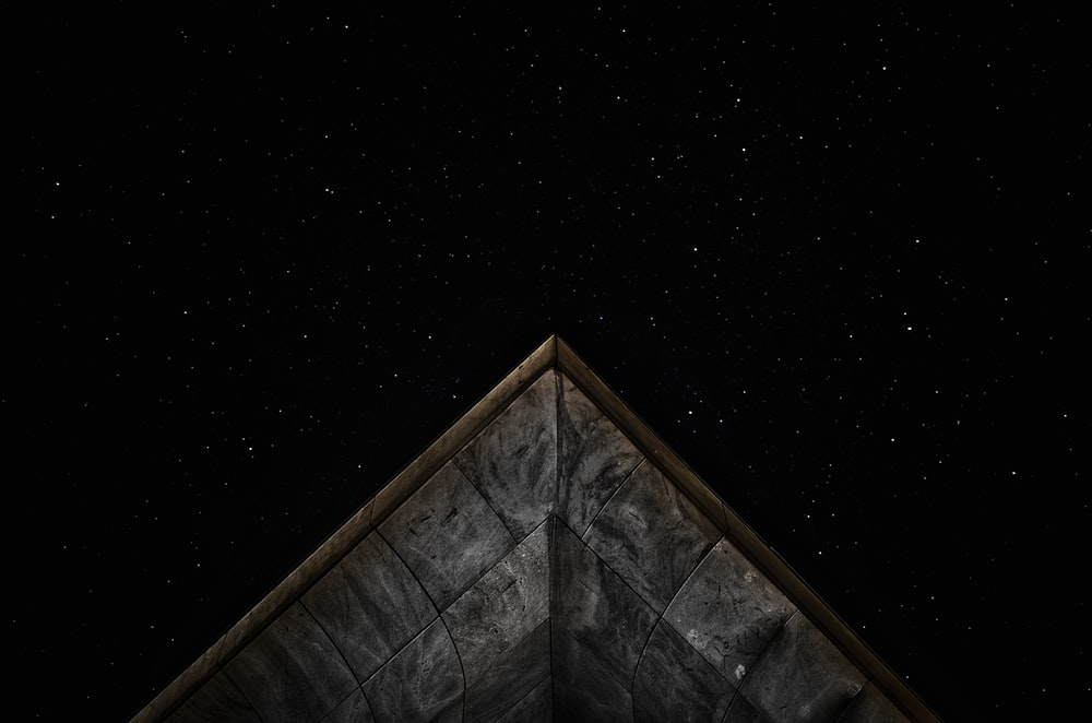 gray roof under starry sky at nighttime