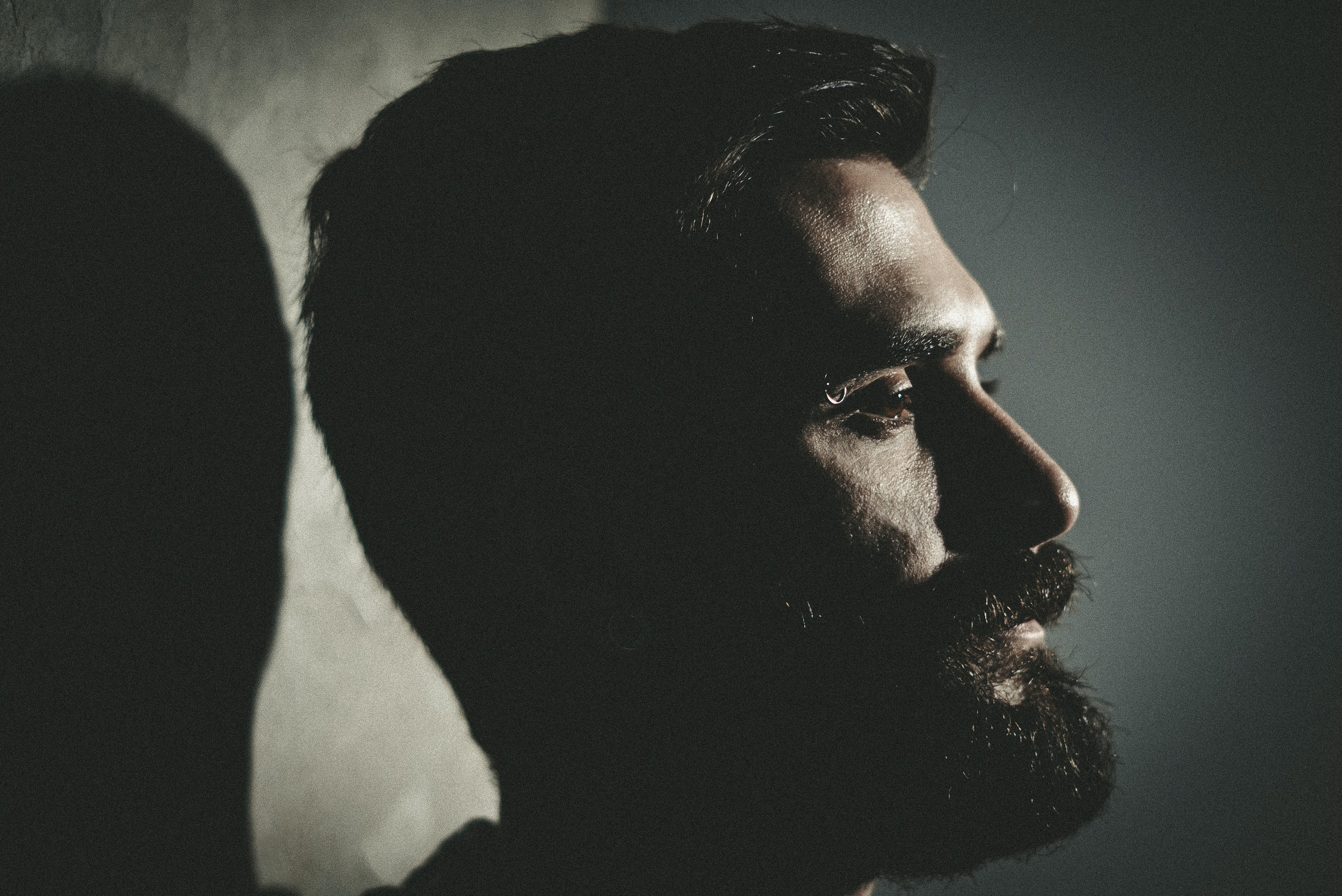 A close-up bearded man with a serious expression casts a shadow