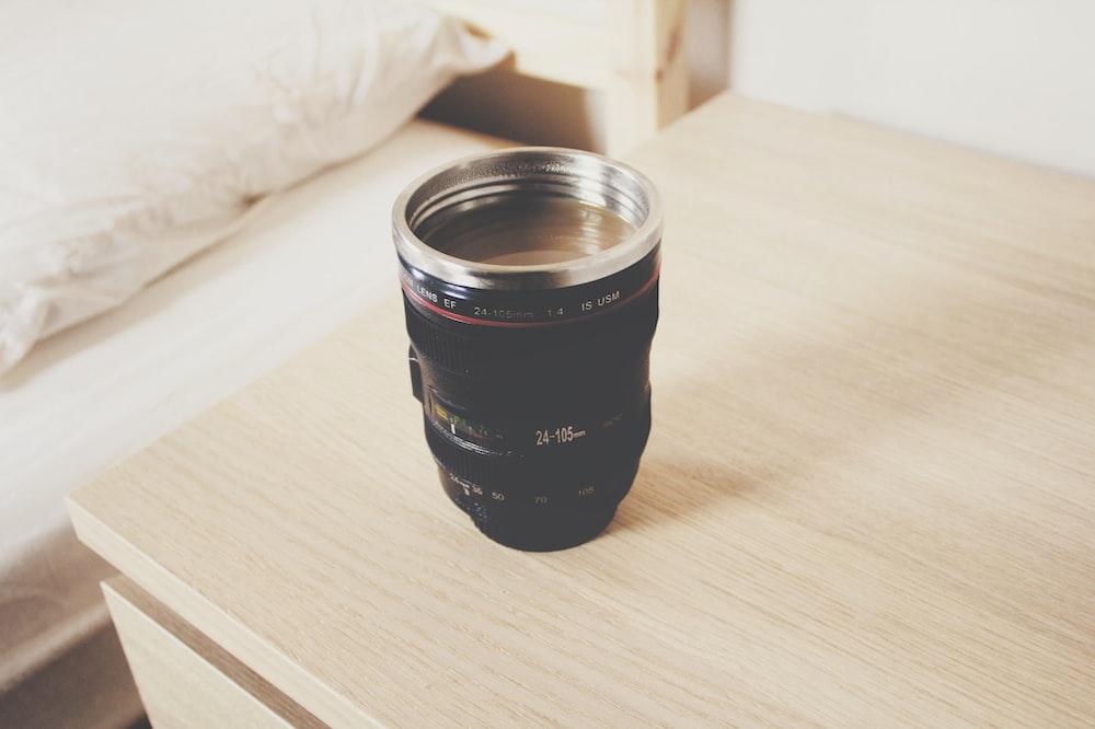 black DSLR camera lens travel mug on nightstand