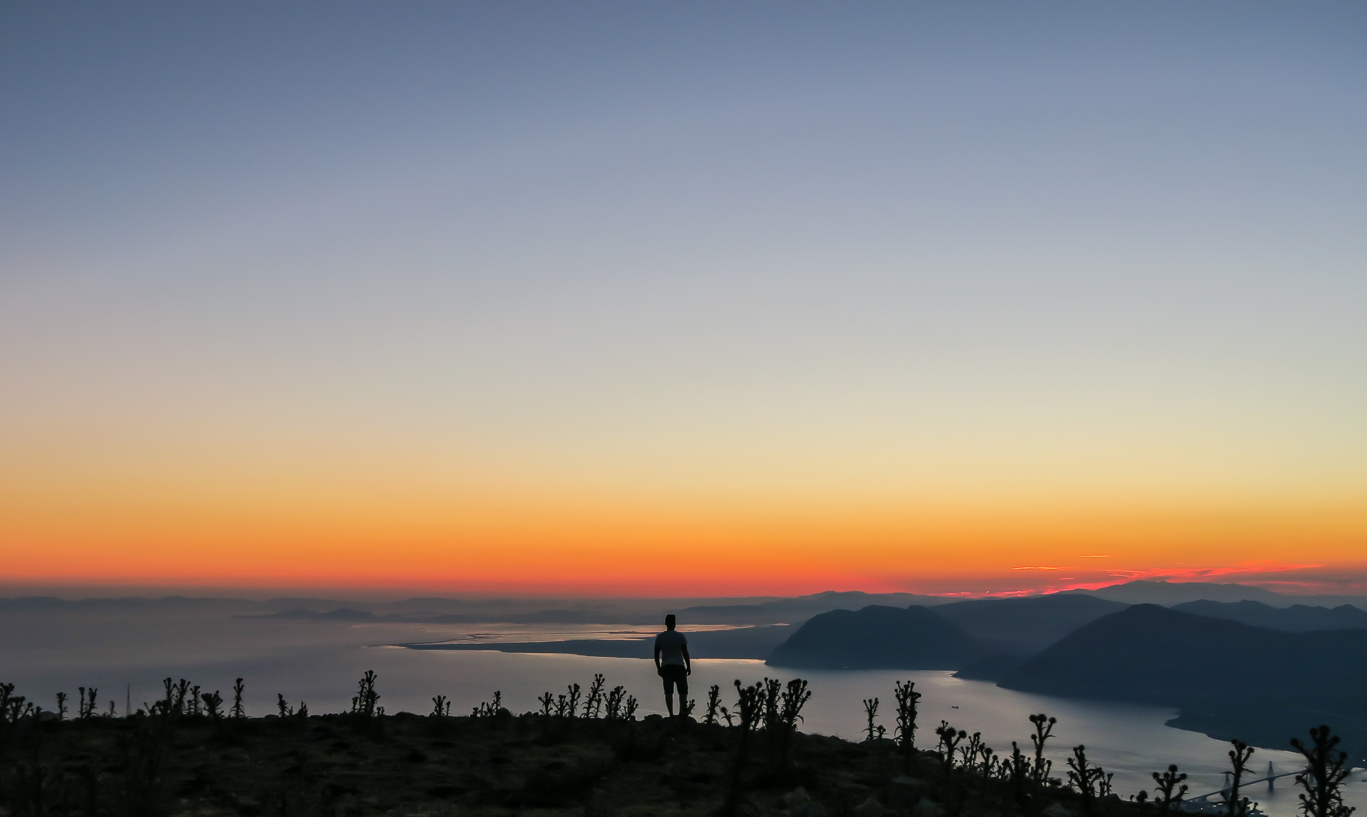 silhouette photo of man standing on mountain