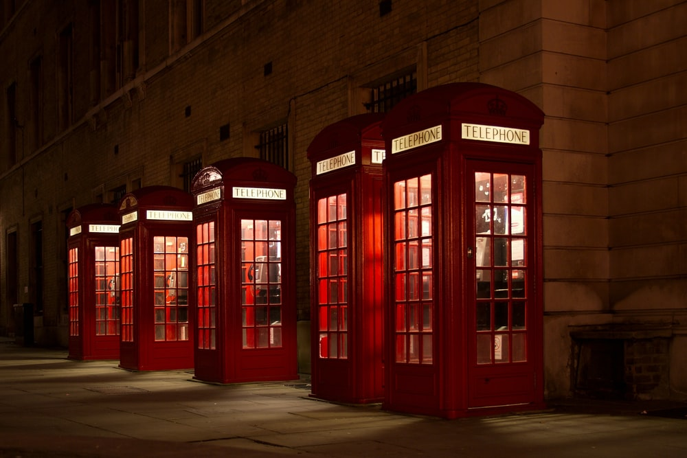 five red lined phone booths near building