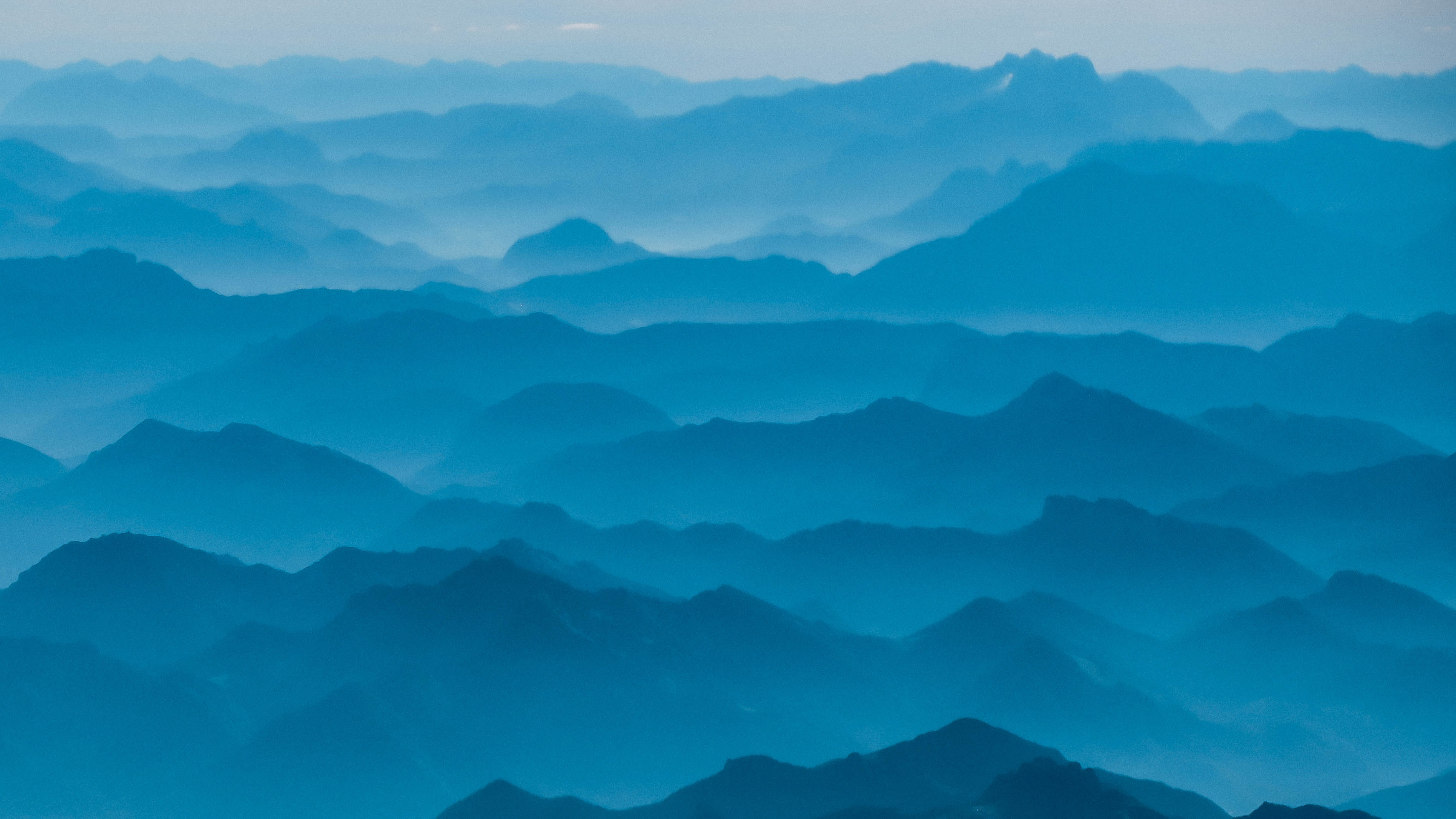 A series of parallel mountain ridges under a blue haze