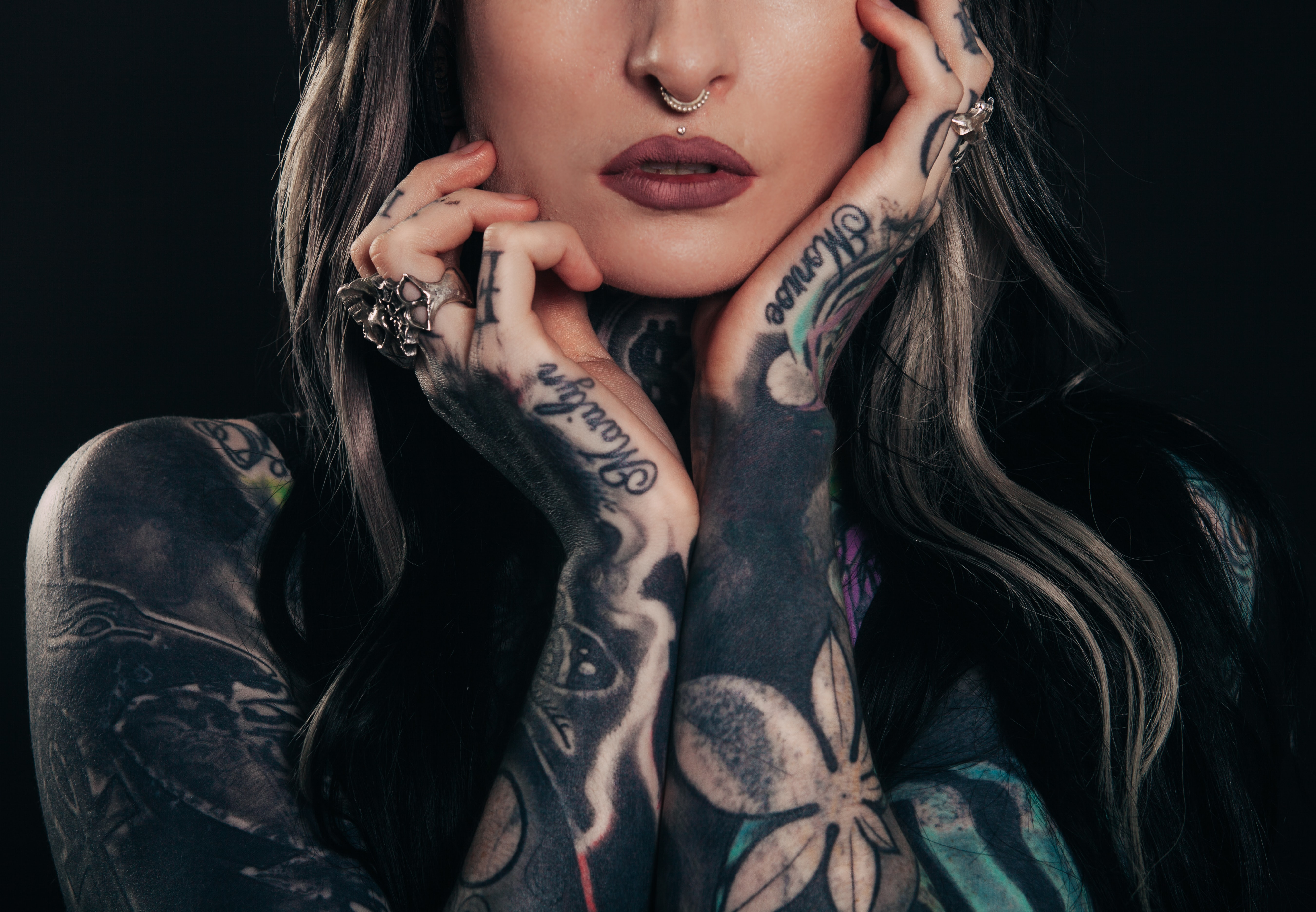 Edgy woman with tattoos and a piercing holds her hands against her face