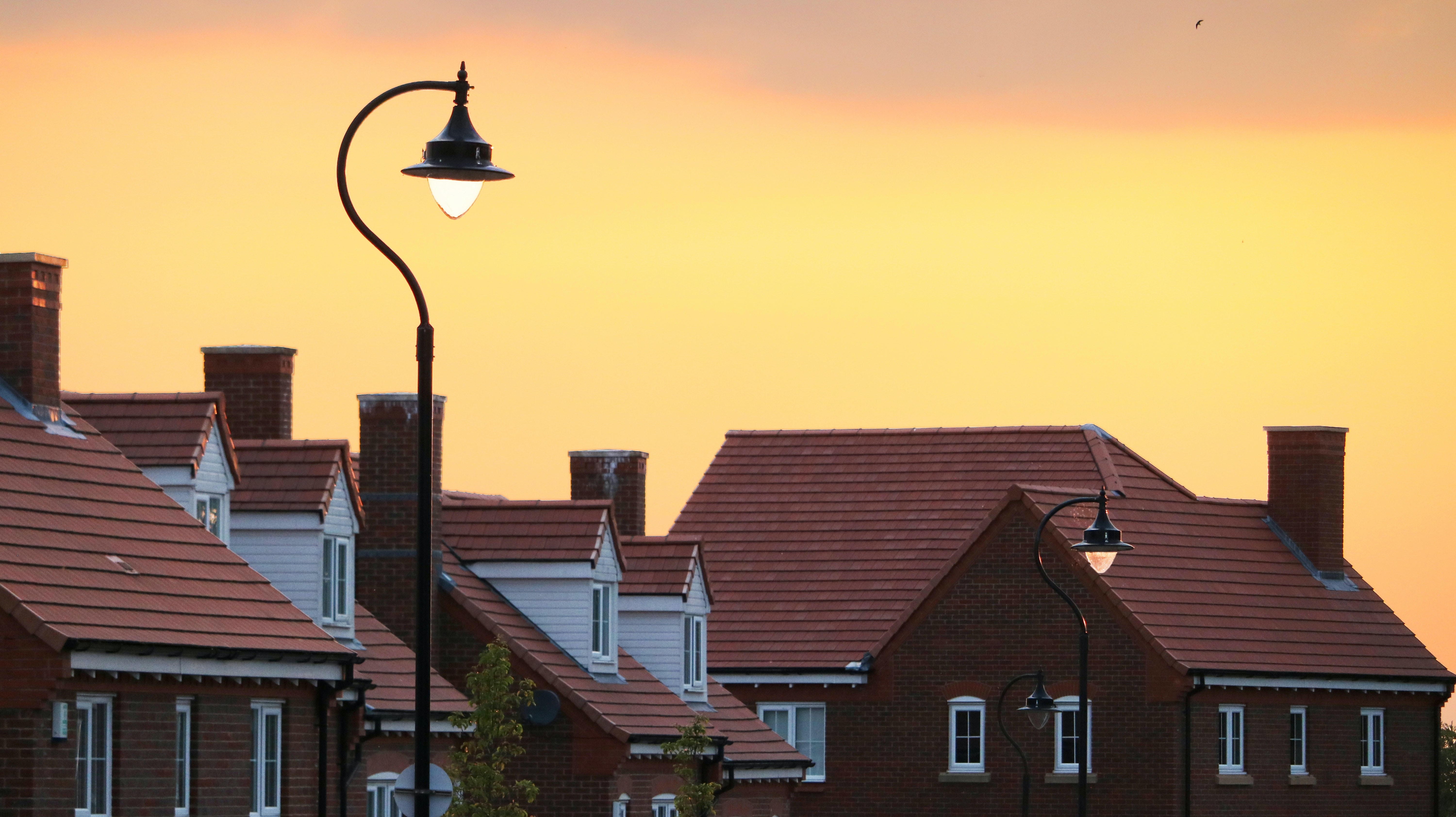 Sun setting over red-roofed village houses behind street lamp