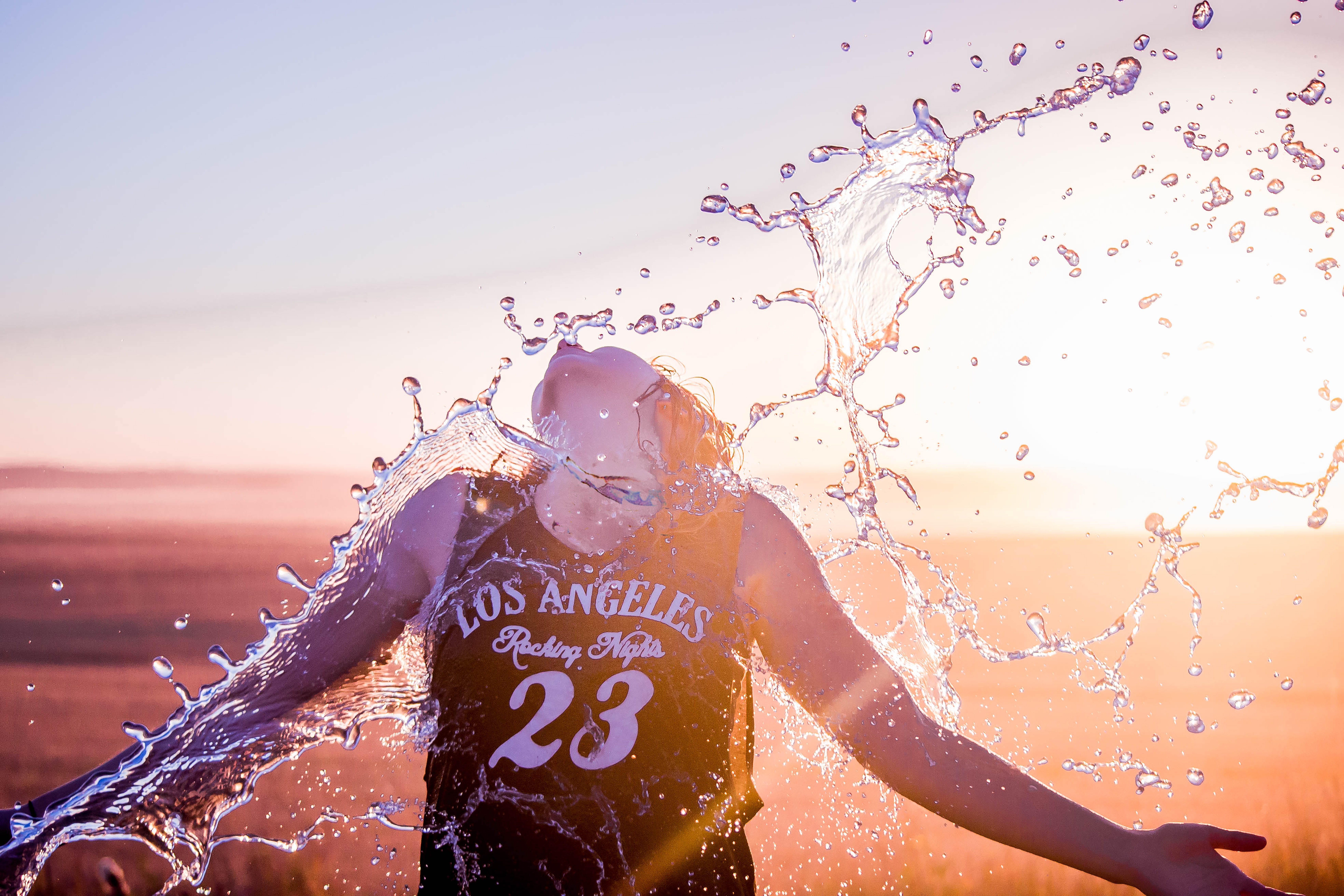 Female wearing a Los Angeles jersey being splashed with water under the sunset in Alberta