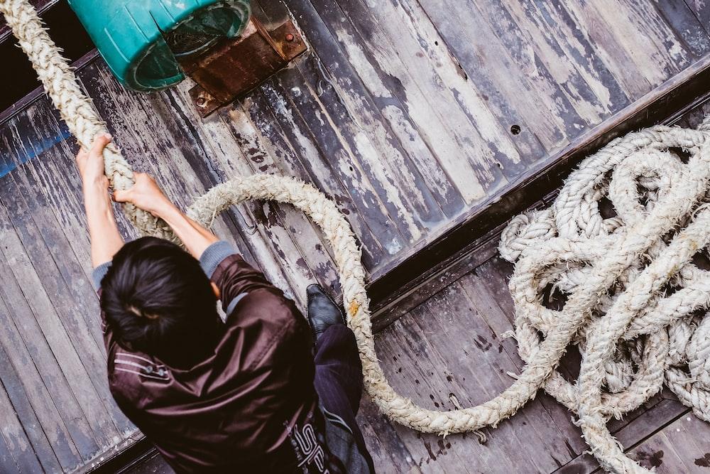 man pulling gray rope