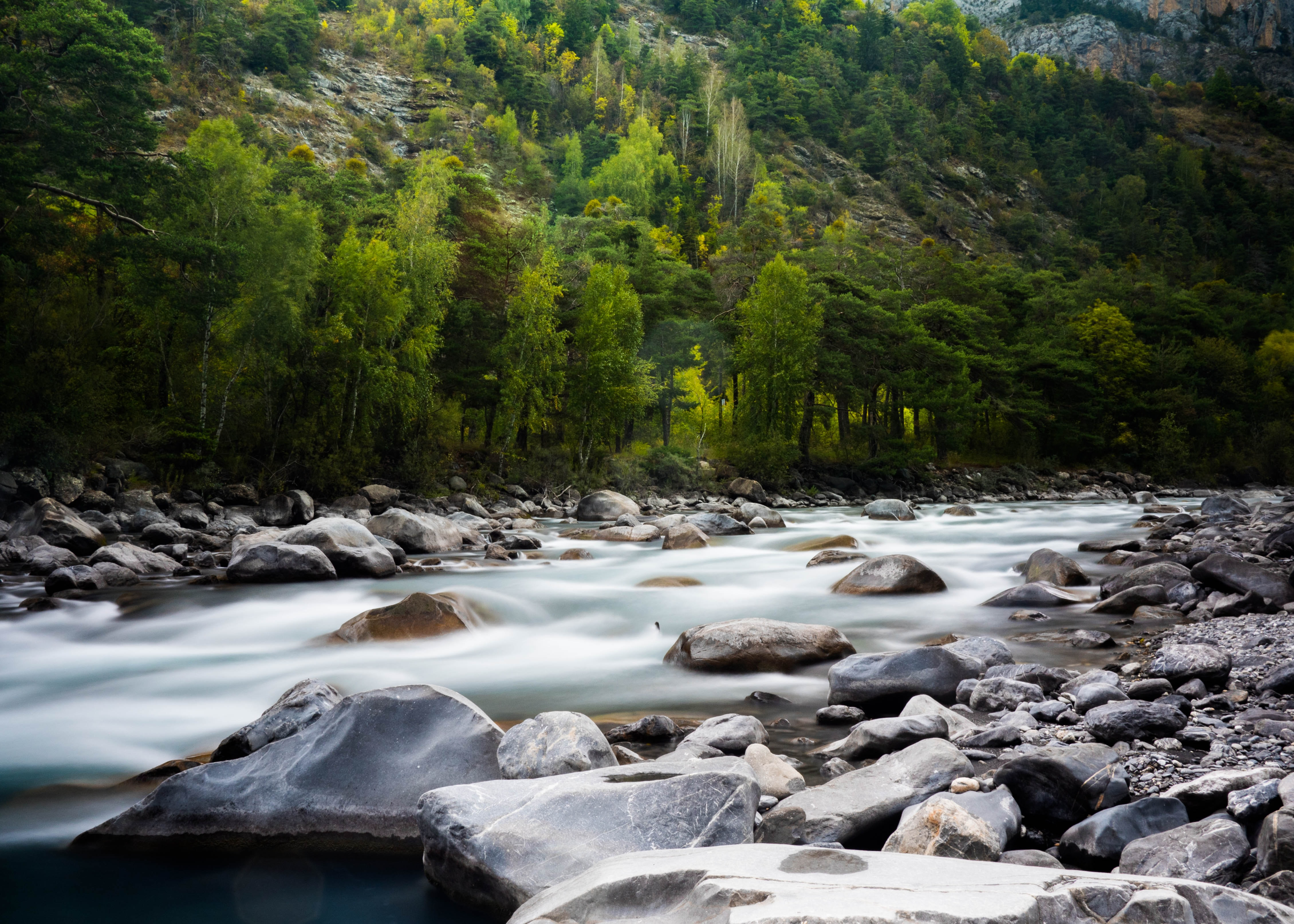 A beautiful background image featuring a stream flowing near a mountain in Col de la Cayolle