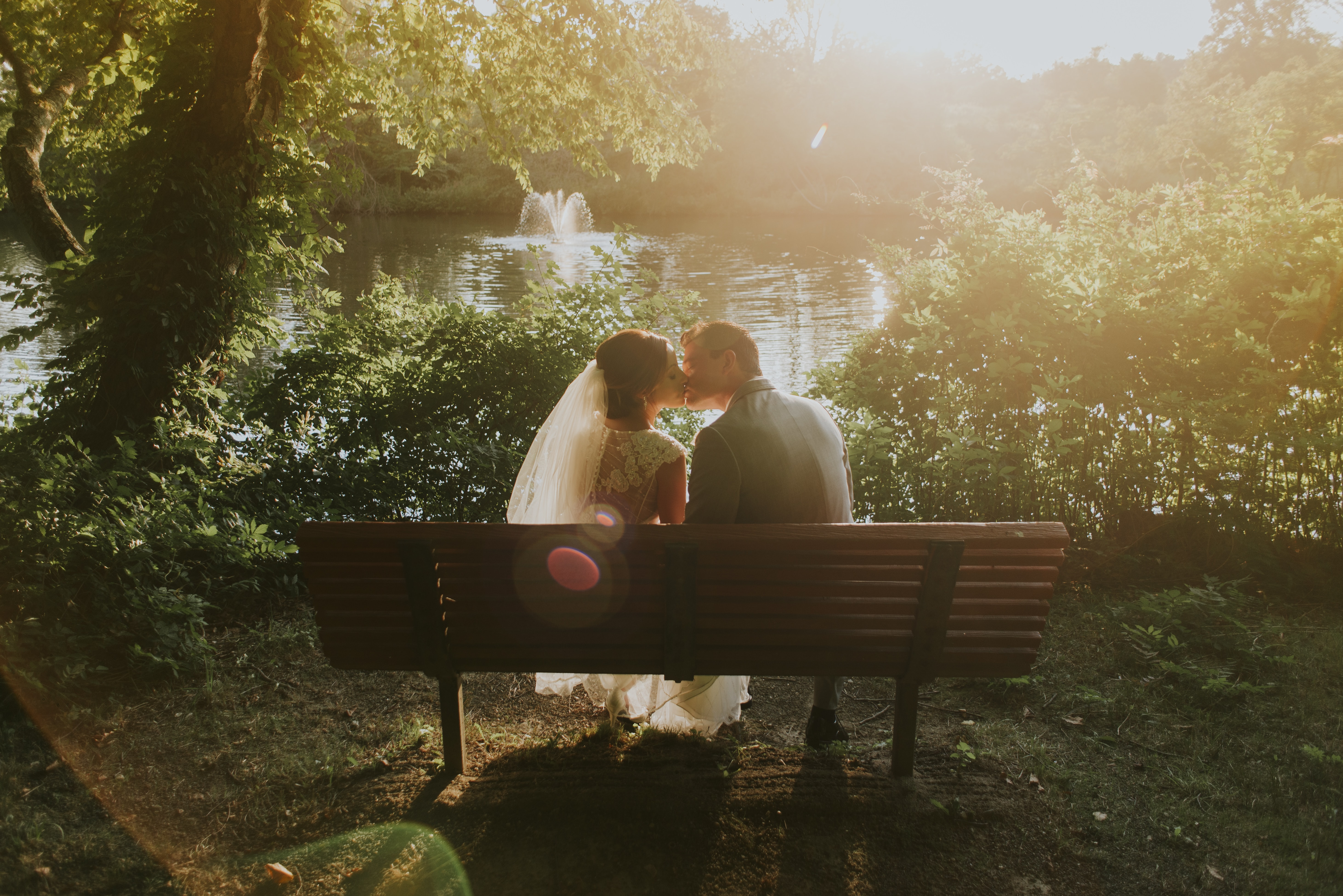Romantic sunlight over a just married couple kissing on a park bench at a lake