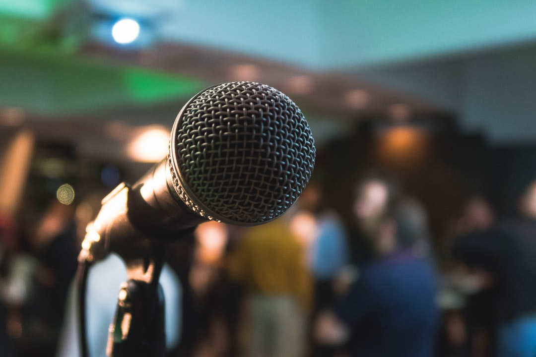 A close-up of a microphone with a group of people in the blurred background