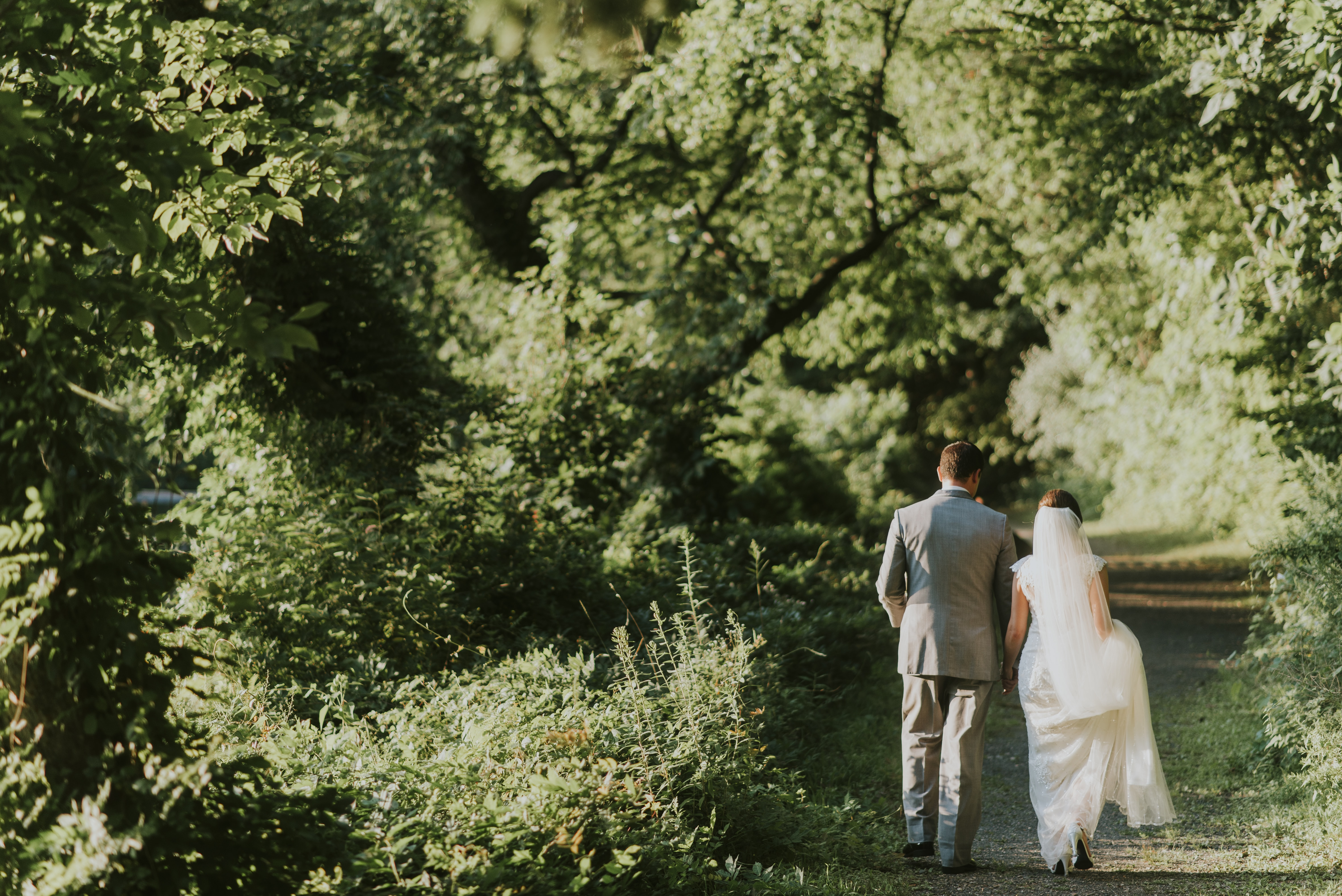 A bridal couple walking on a dirt path lined with trees